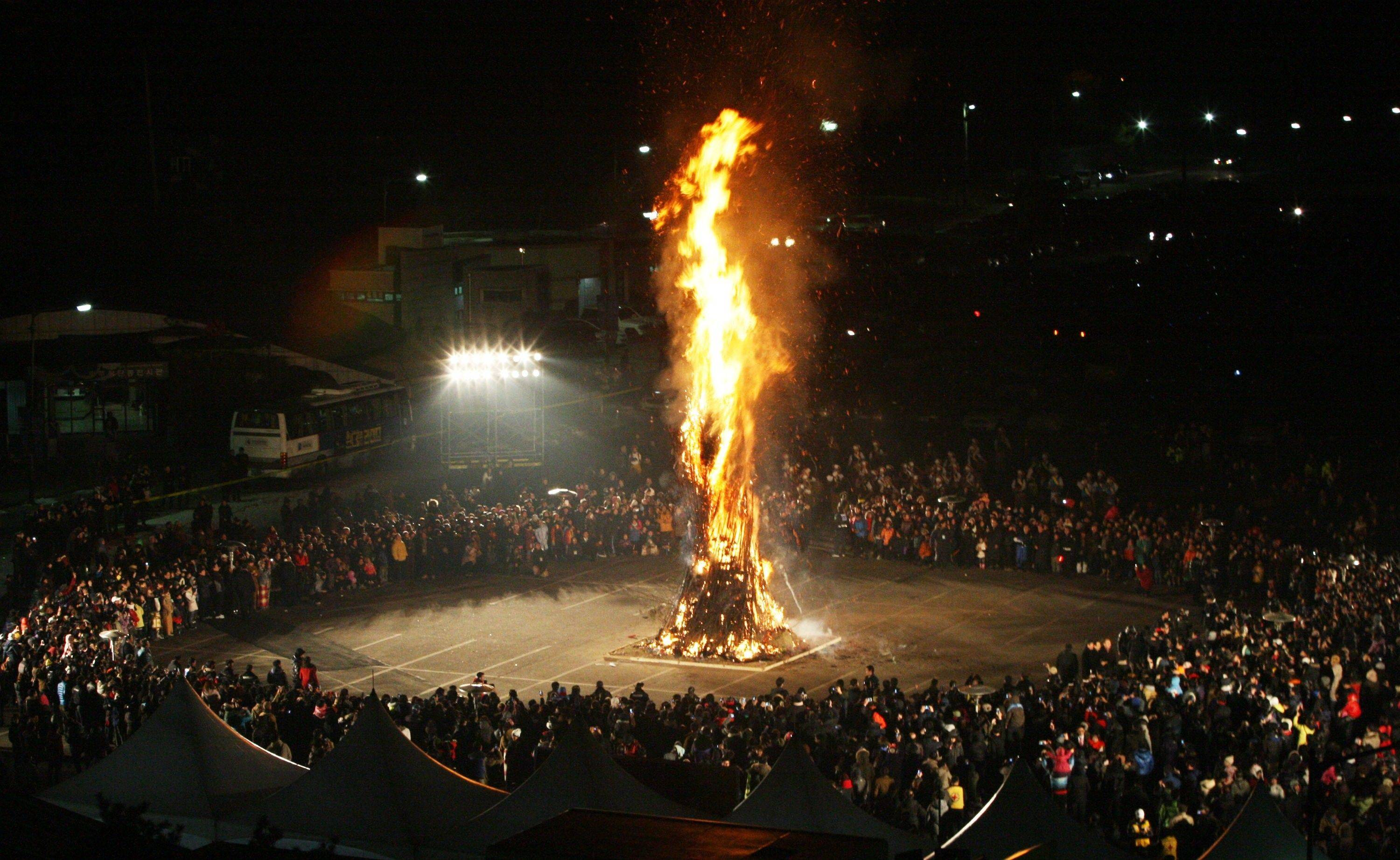South Koreans view the burning of Daljips, a wooden hut built on top of a hill, to celebrate the New Year near the border village of Panmunjom (DMZ) that separates the two Koreas since the Korean War, at Imjingak Pavilion in Paju, South Korea, Sunday, Jan. 1, 2012.