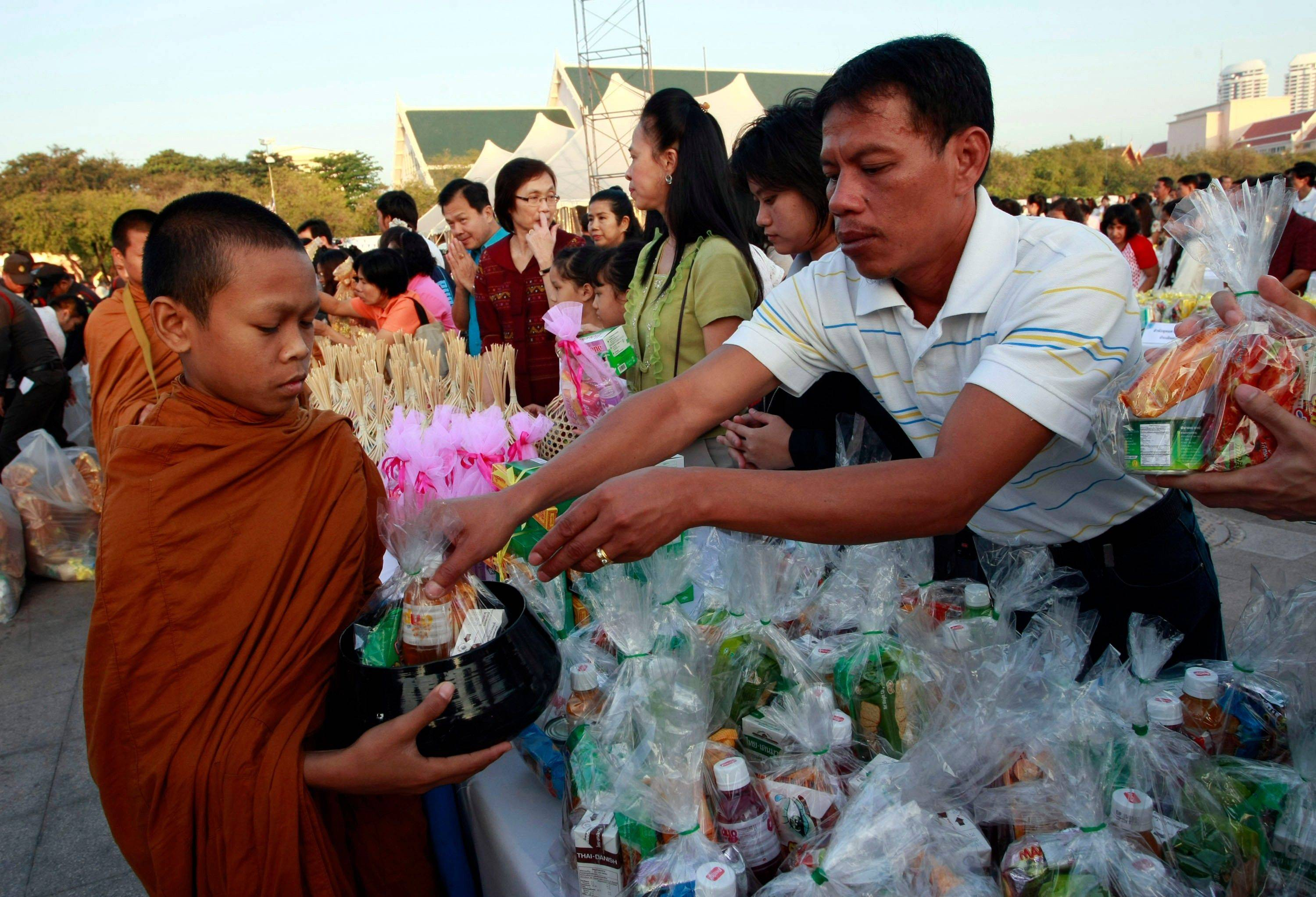 A Buddhist monk takes up alms from Thais during a morning alms offerings, part of New Year's celebrations, Sunday, Jan. 1, 2012 in Bangkok, Thailand.