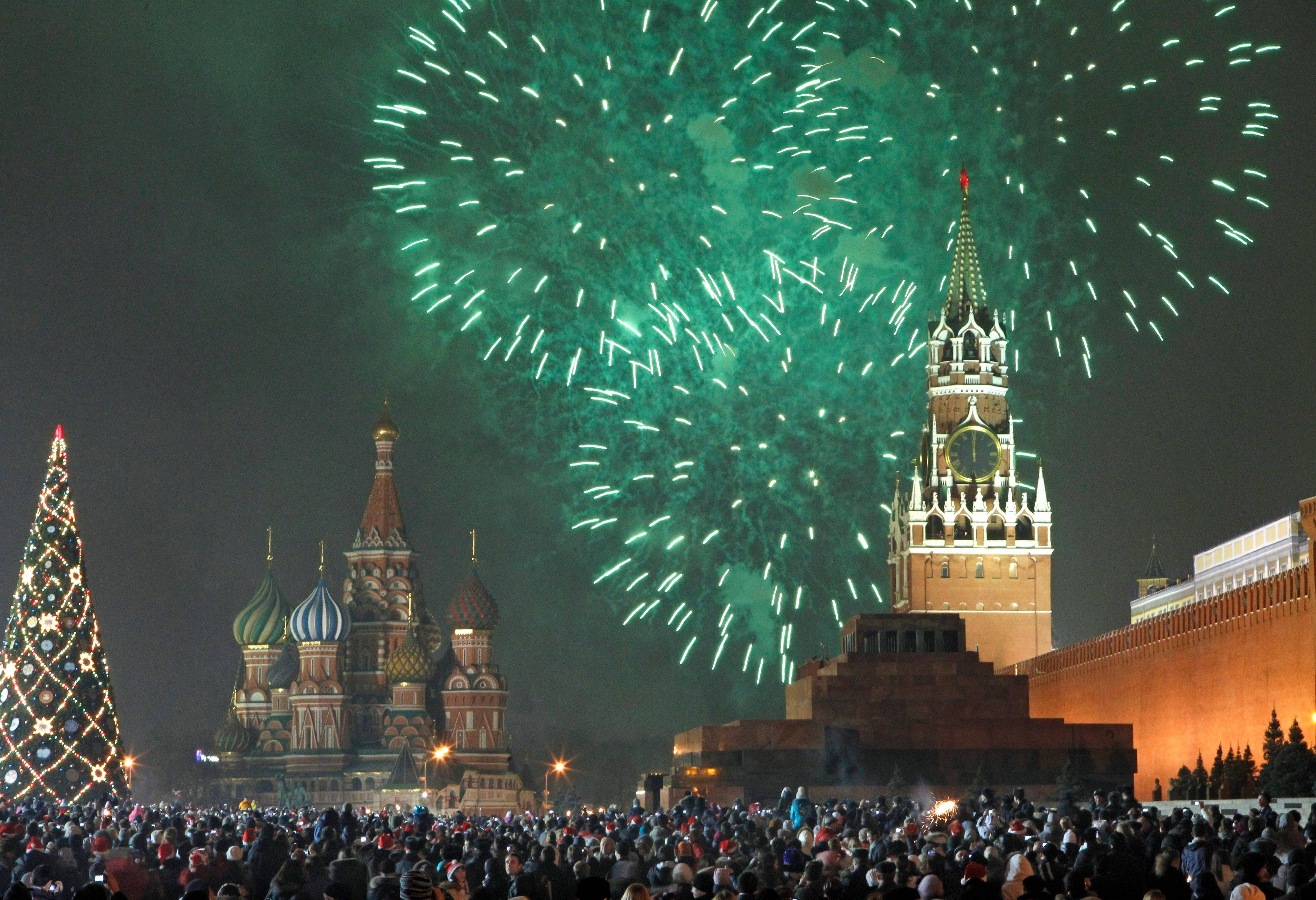 Russians celebrate the New Year on Sunday on Red Square in Moscow, with the Kremlin in the background, right, and St. Basil's cathedral in background left, Russia. Tens of thousands of people gathered on the Square to celebrate the new year, and view the fireworks as the clock on the Kremlin's Spassky Tower, right, struck midnight.