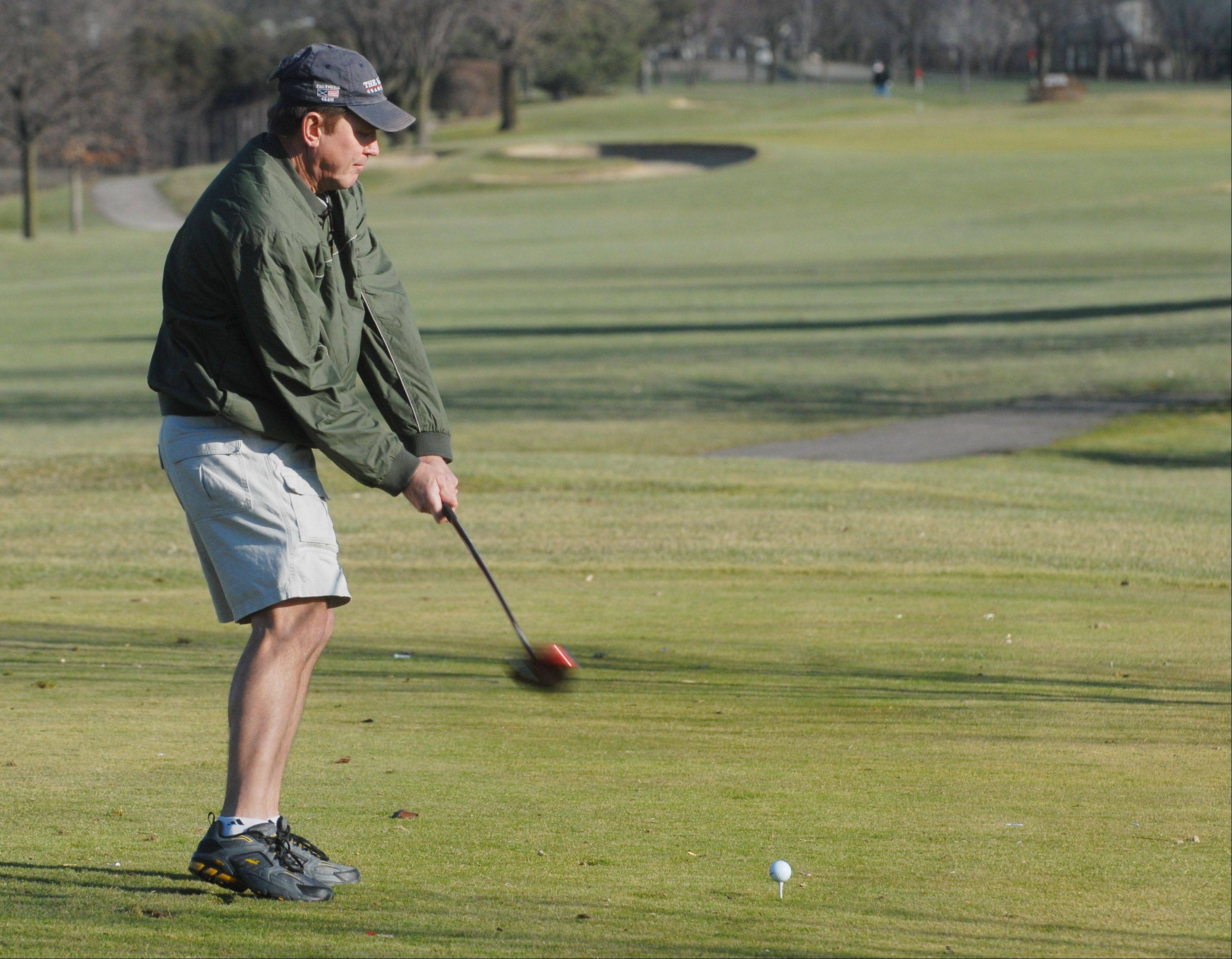 Kenny Geheb of Palatine tees off while playing in shorts at the Arlington Lakes Golf Club in Arlington Heights Thursday.