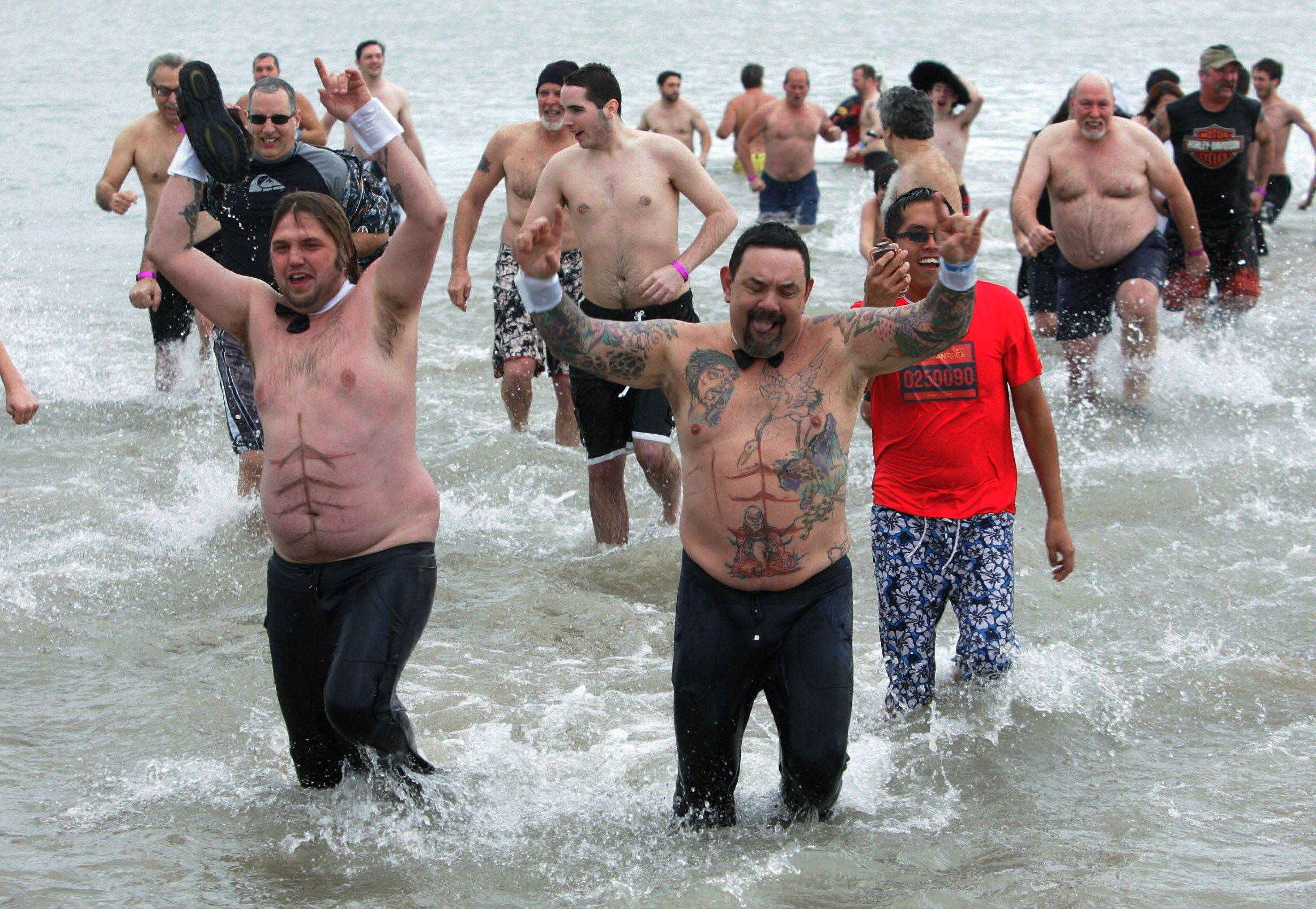 Costumed Daniel Reppert, left, of McHenry and John Sota of Zion lead a crowd out of the water during the 13th Annual Polar Bear Plunge Sunday in Waukegan.