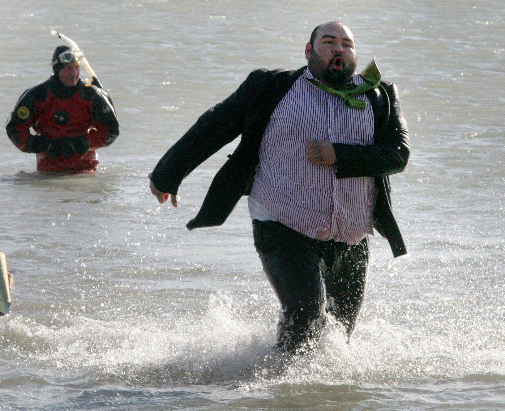 Alex Mancilla of Elgin wears a suit as he runs out of the water after a frigid morning dip during the 13th Annual Polar Bear Plunge Sunday in Waukegan.