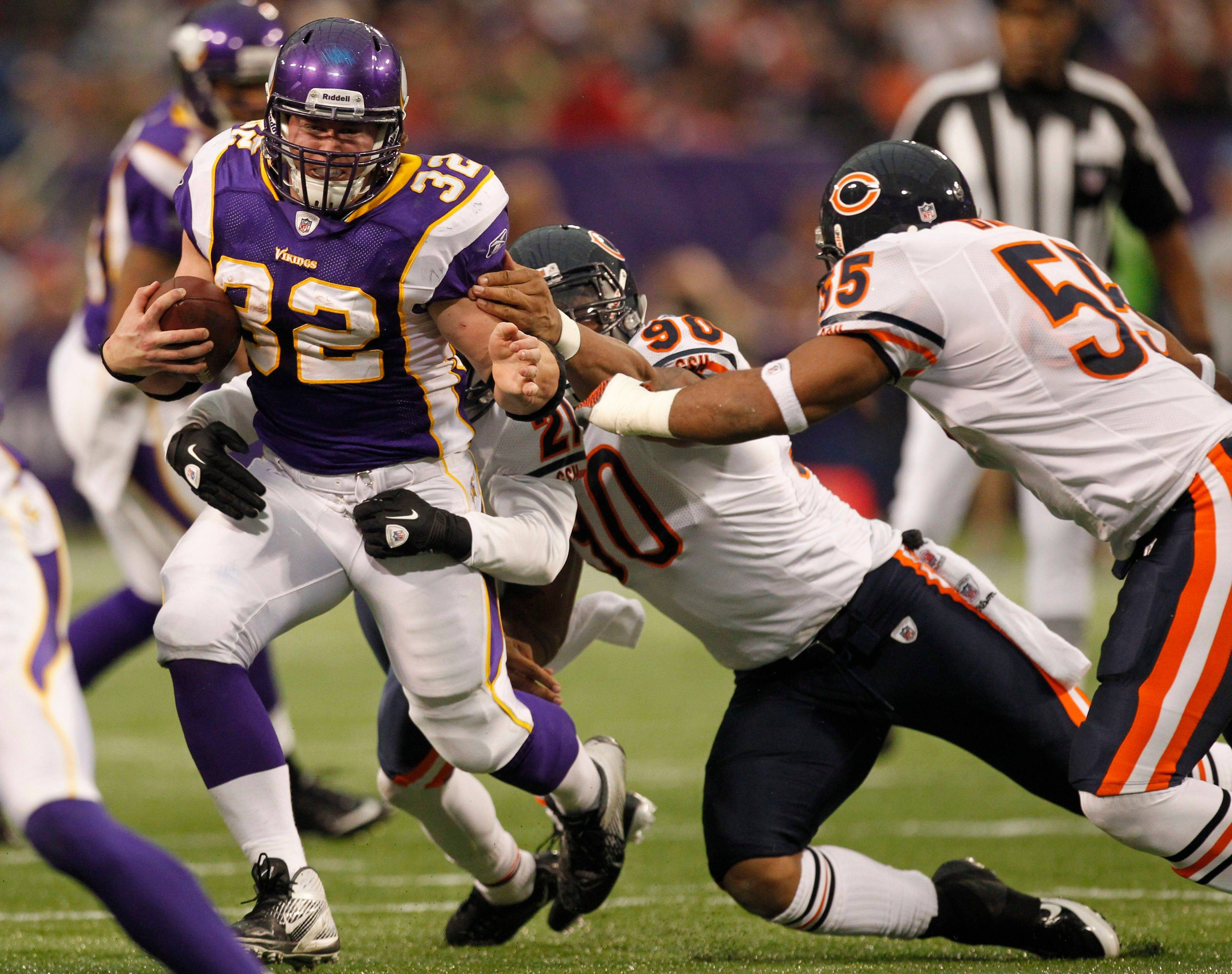 Minnesota Vikings running back Toby Gerhart gets tackled by Chicago Bears defensive back Corey Graham and defensive end Julius Peppers in the first half.
