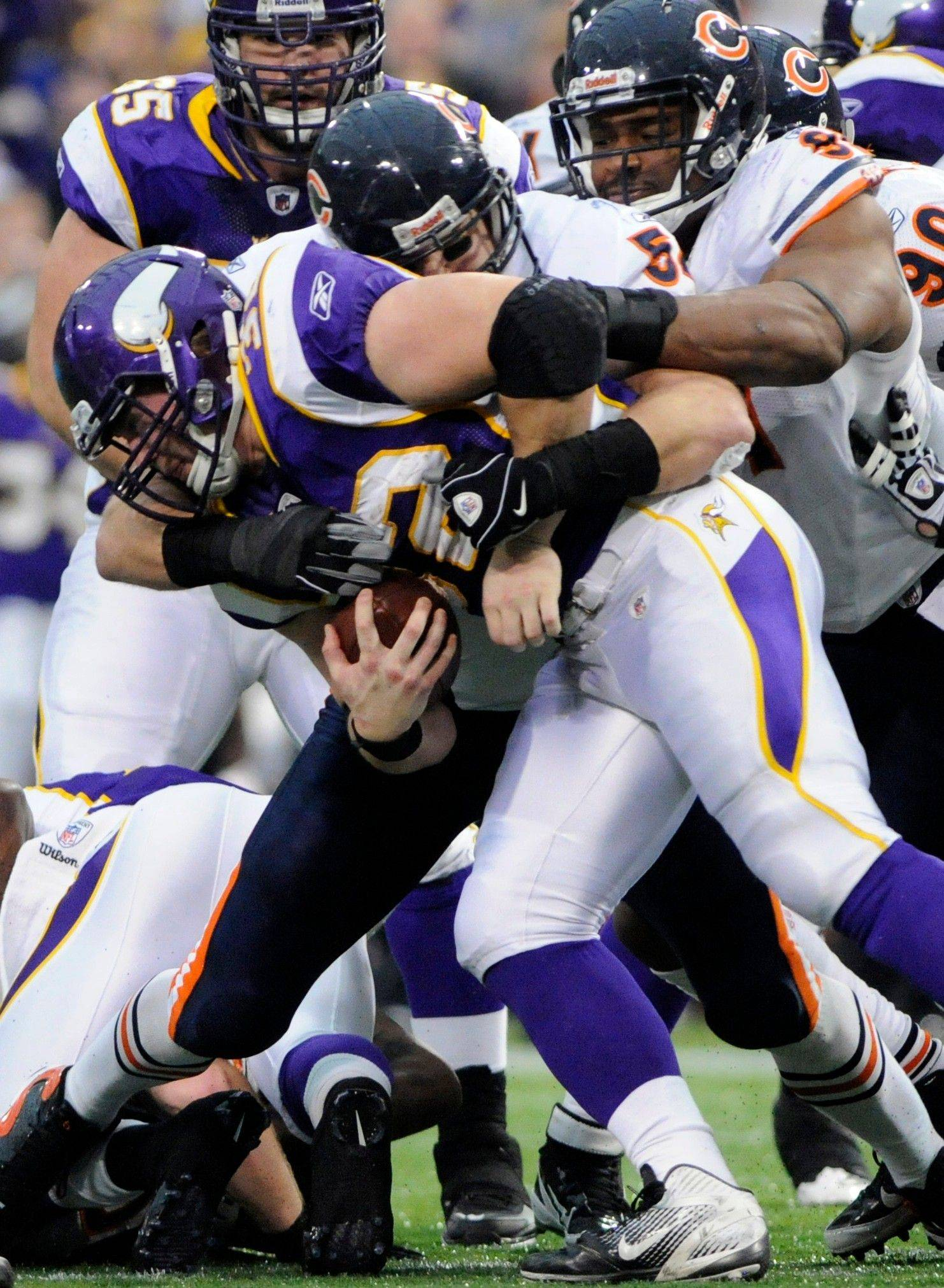 Minnesota Vikings running back Toby Gerhart gets tackled by Chicago Bears middle linebacker Brian Urlacher and defensive tackle Amobi Okoye in the first half.