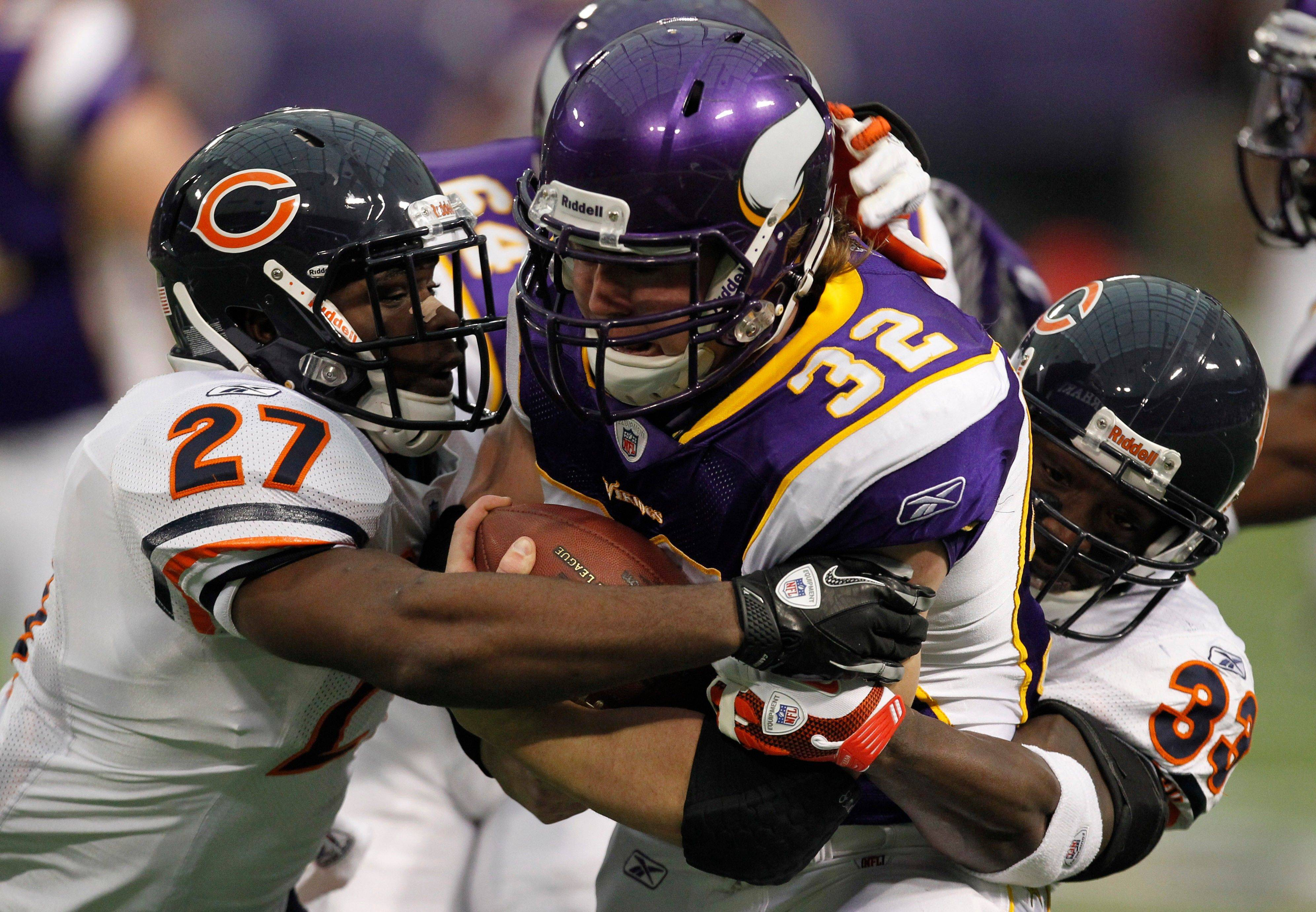 Minnesota Vikings running back Toby Gerhart is tackled by Chicago Bears strong safety Major Wright and cornerback Charles Tillman in the first half.