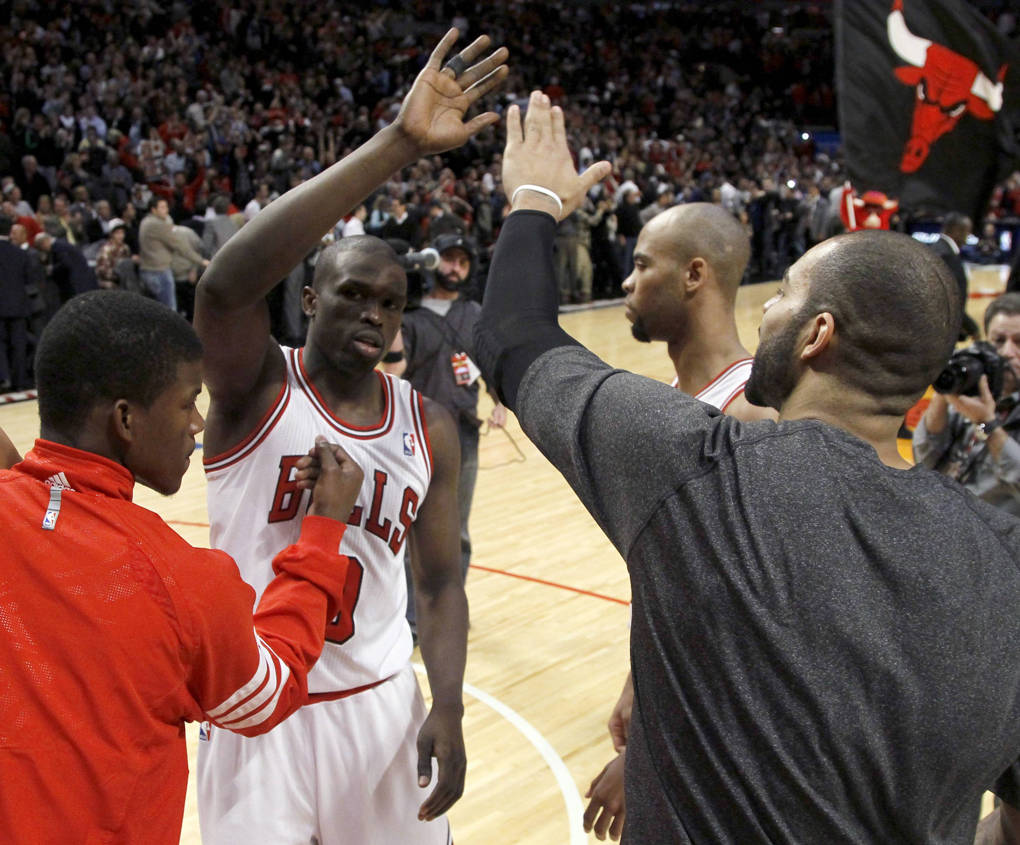 Chicago Bulls small forward Luol Deng, second from left, celebrates with Jimmy Butler, left, Taj Gibson, second from right, and Carlos Boozer after their 76-74 come-from-behind win over the Atlanta Hawks on Tuesday in Chicago.