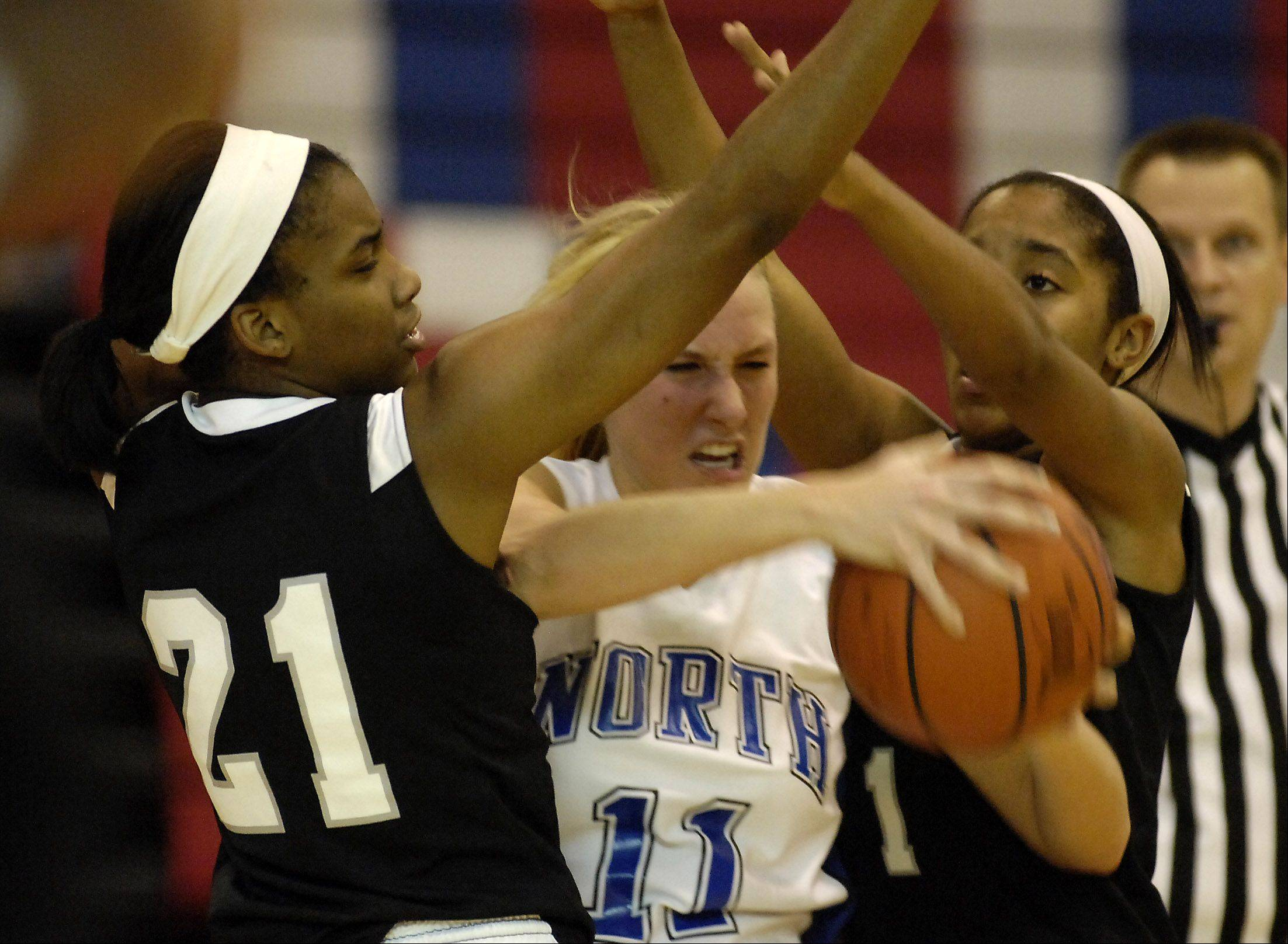St. Charles North's Megan Booe, center, tries to pass the ball with Fenwick's Maya Garland,left, and Jade Owens defending during Monday's basketball game in Carpentersville.