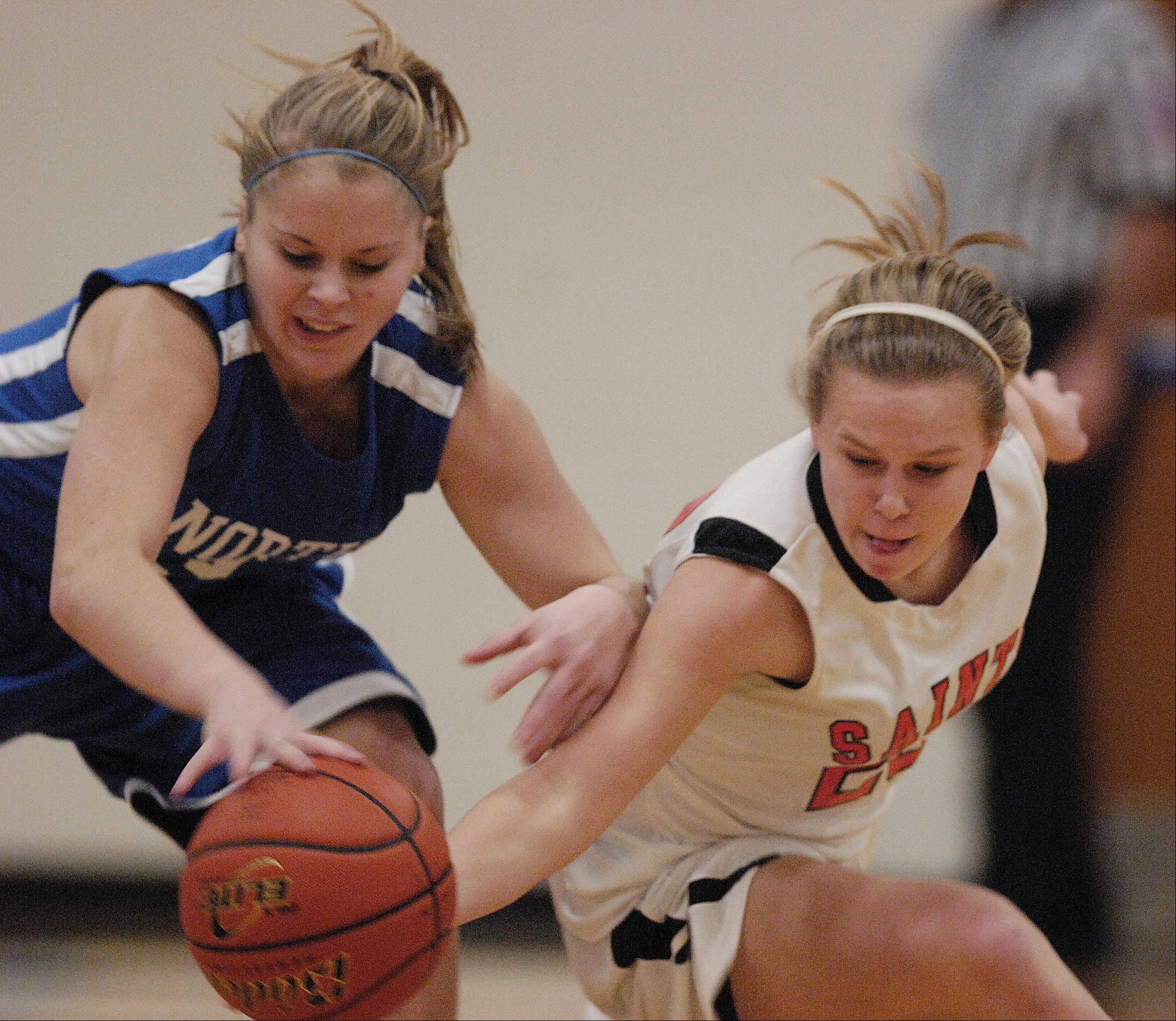 Wheaton North;s Reilly Stewart and St. Charles East's Amanda Hilton chase a loose ball during the Bill Neibch Holiday girls basketball tournament Monday at Wheaton North High School.