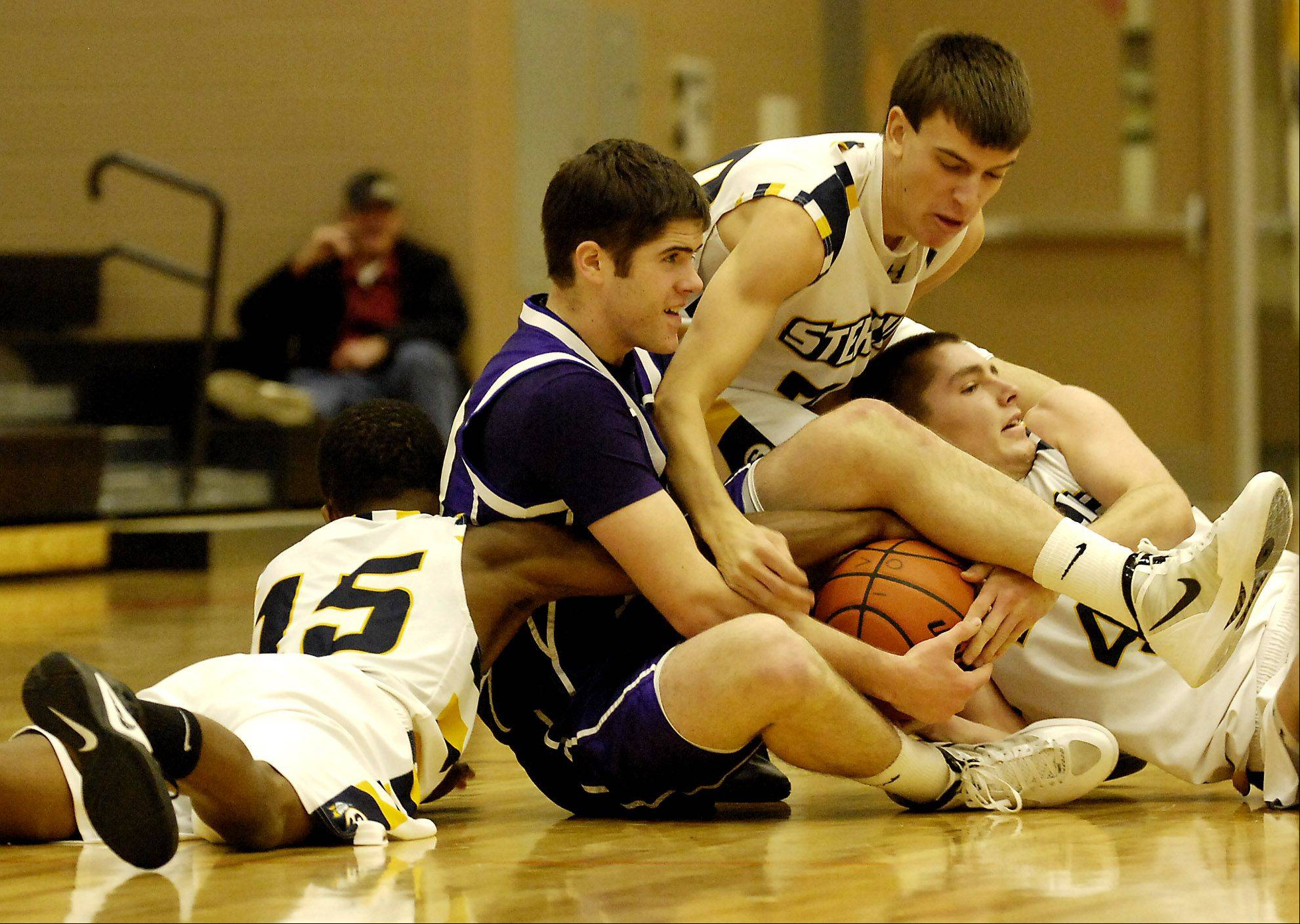 Hampshire's Tyler Crater battles Sterling's Cornell Hartz, left, Nathan Blackburn, middle, and Patrick Petrosky, right, for a loose ball during Wednesday's basketball game Wednesday in Dekalb.