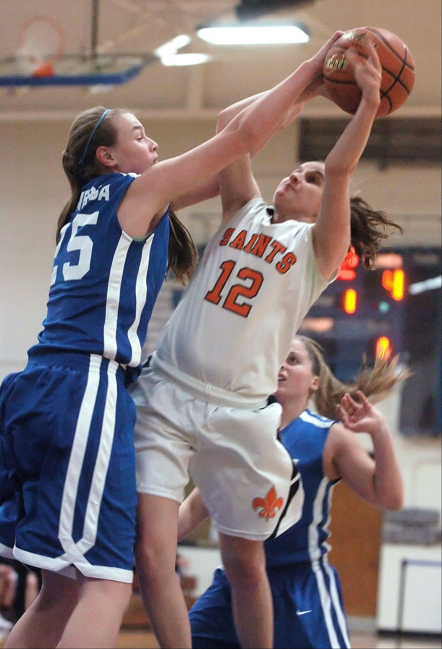 Wheaton North's Annie Carlisle blocks a shot by St. Charles East's Paige Jordan during Monday's Bill Neibch Holiday girls basketball game at Wheaton North High School.