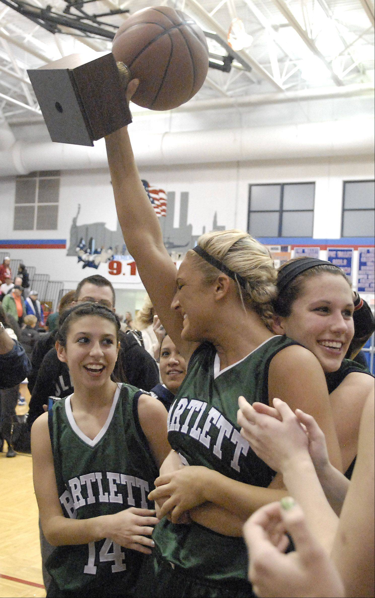 Bartlett's Haley Videckis hoists the trophy after the Hawks won the championship game over New Trier Thursday at Dundee-Crown's girls basketball tournament in Carpentersville.