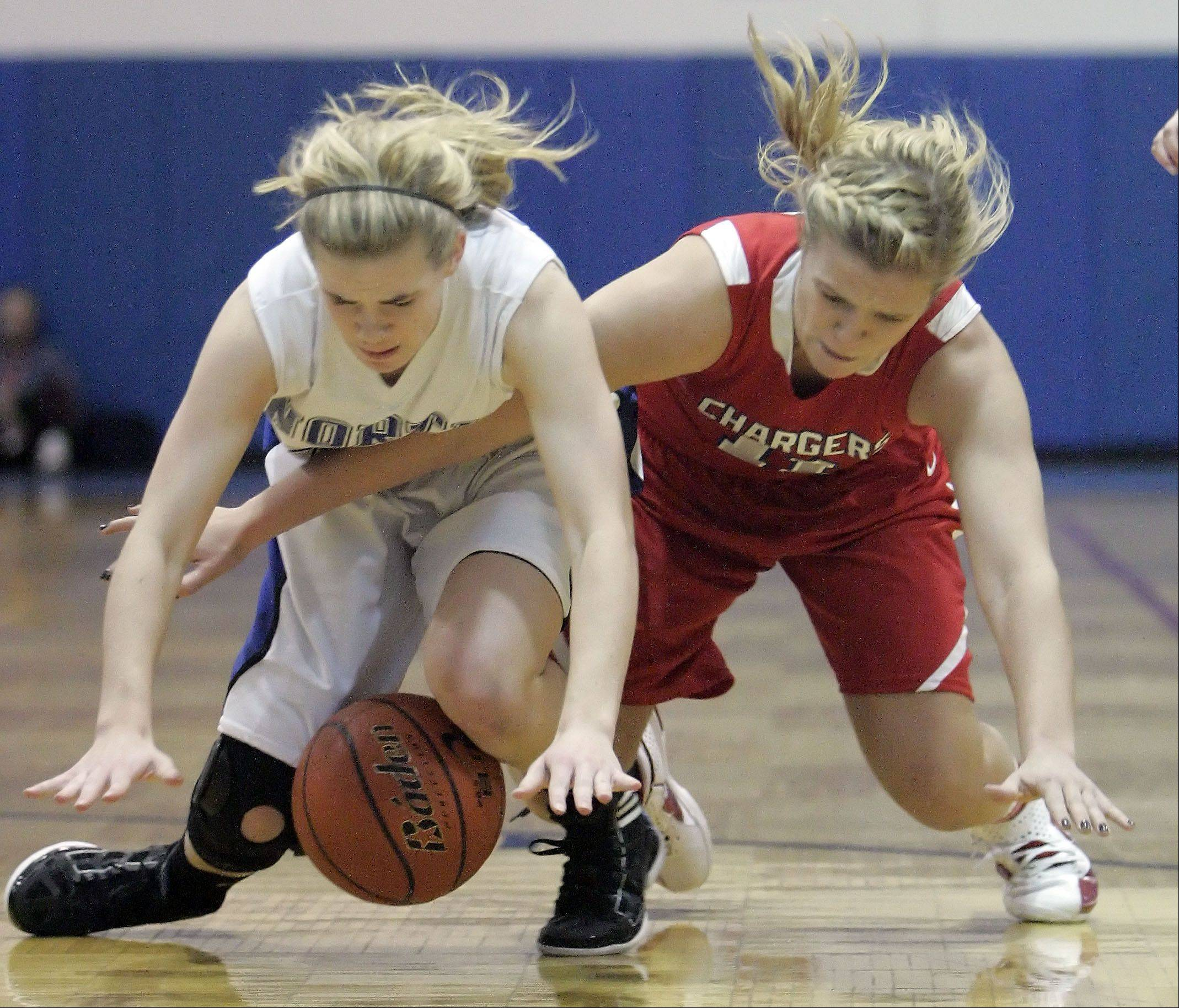 Dundee-Crown's Ali Sanders, 11, wrestles with St. Charles North's Lauren Durocher, 24, for the ball at the Dundee-Crown High School 29th Annual Charger Classic Christmas Tournament Thursday in Carpentersville.