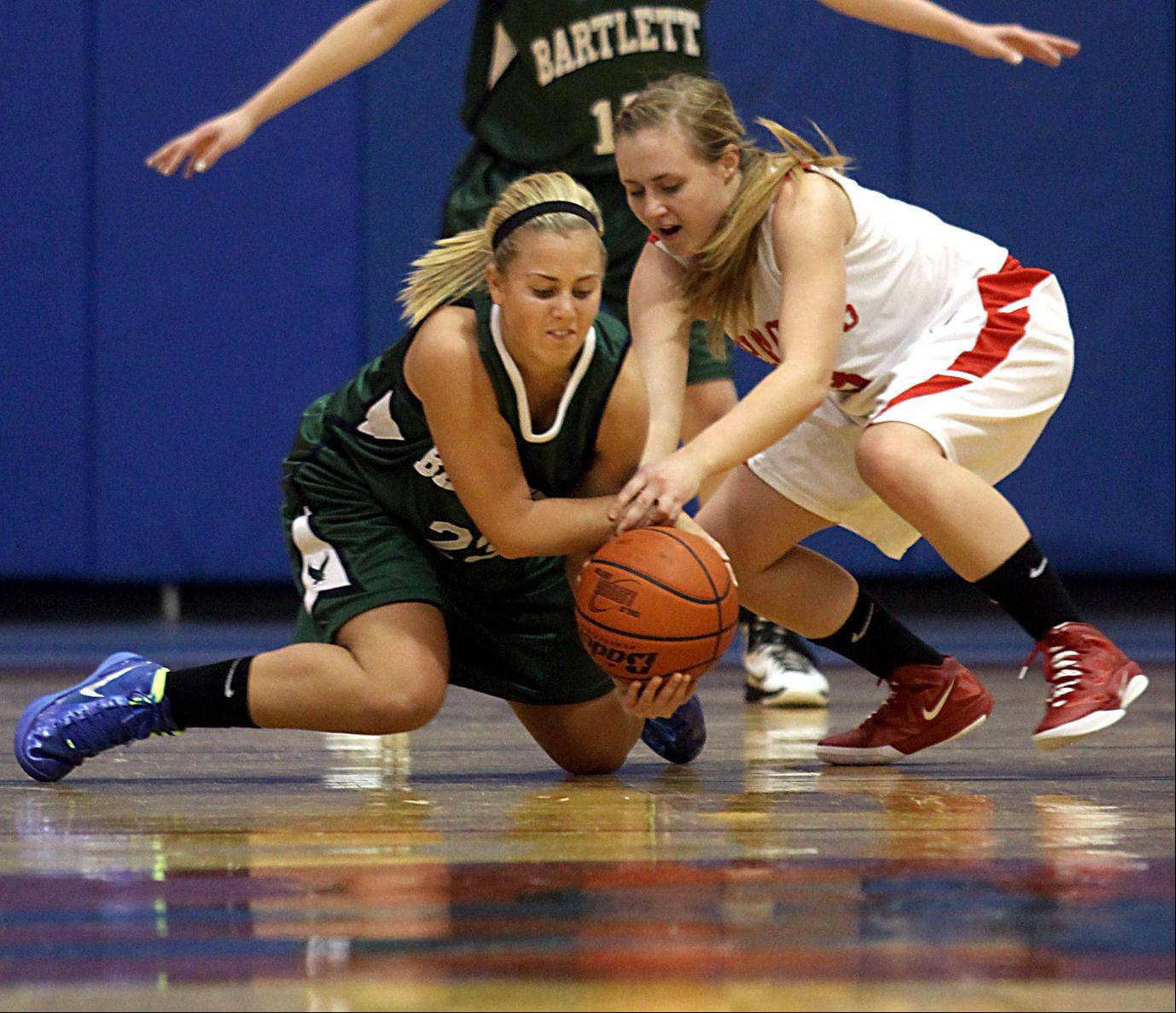 Dundee-Crown's Carlin Faulkner, right, and Bartlett's Ashley Johnson, left, scramble for a loose ball during Monday's basketball game in Carpentersville.
