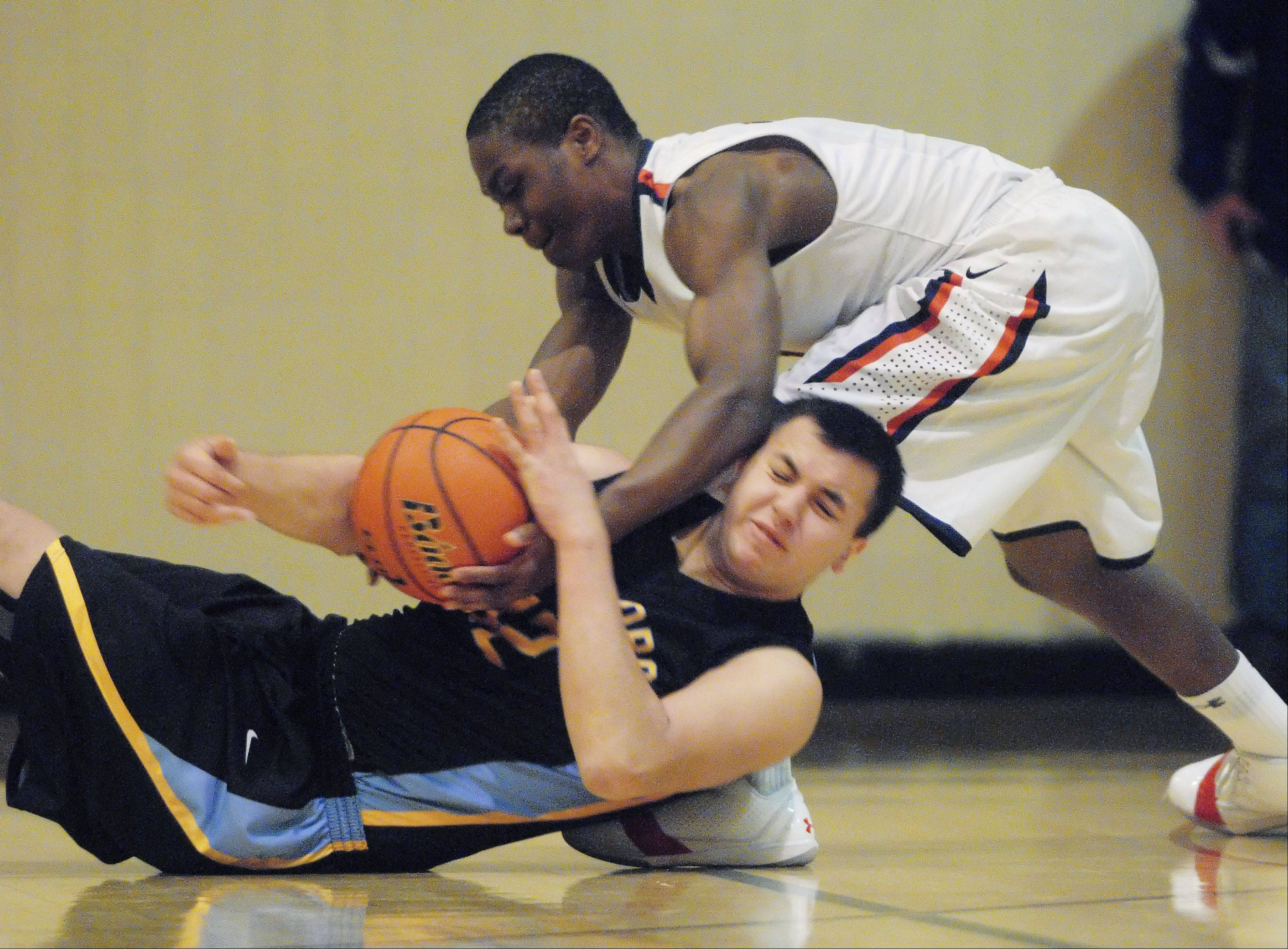 St. Viator's Mayo Arogundade steals the ball from Maine West's Matt Solis during Tuesday night's basketball game in Wheeling.