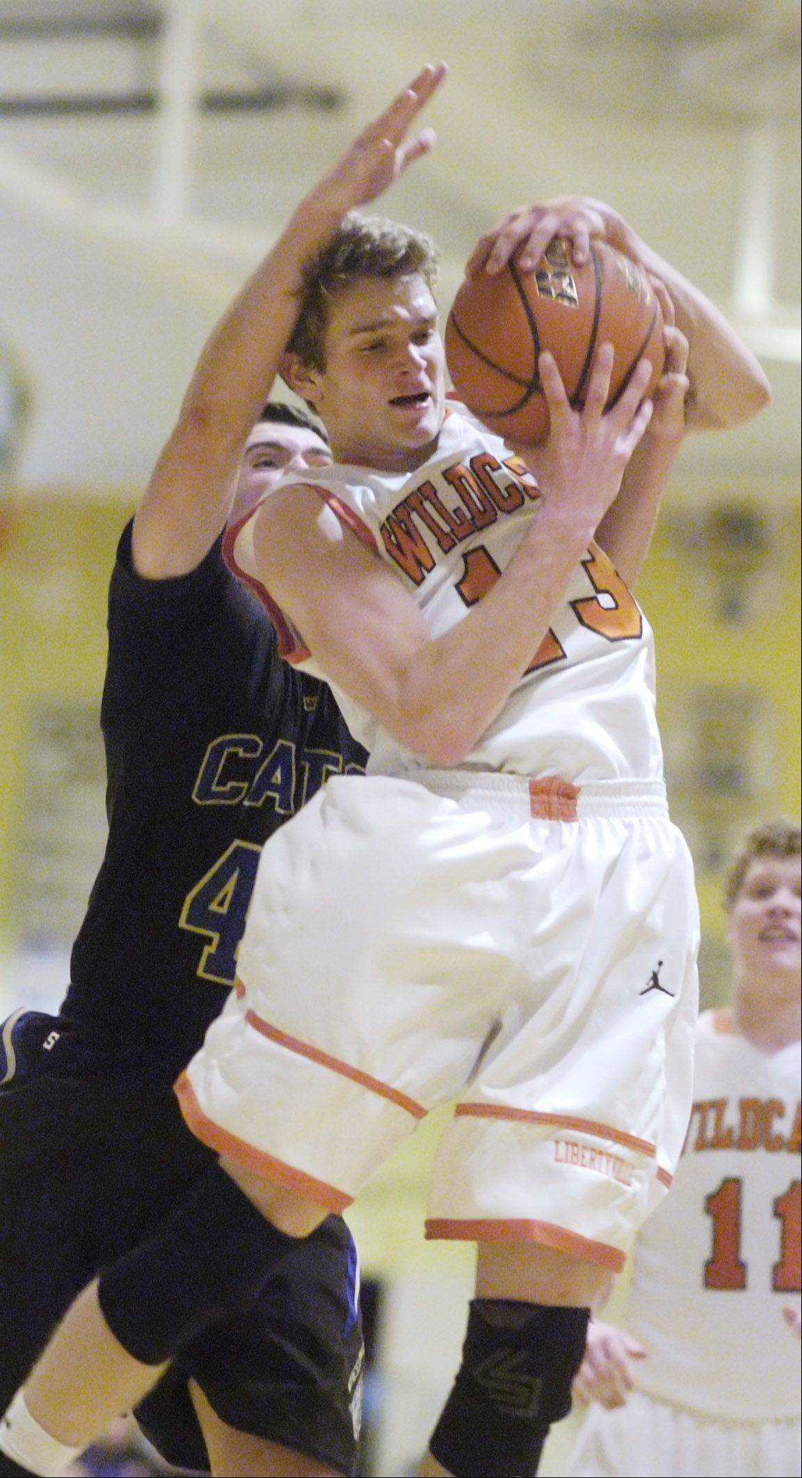 Libertyville's Anthony Mack, right, grabs a rebound in front of Wheeling's Charlie Kirk during Tuesday's basketball game in Wheeling.