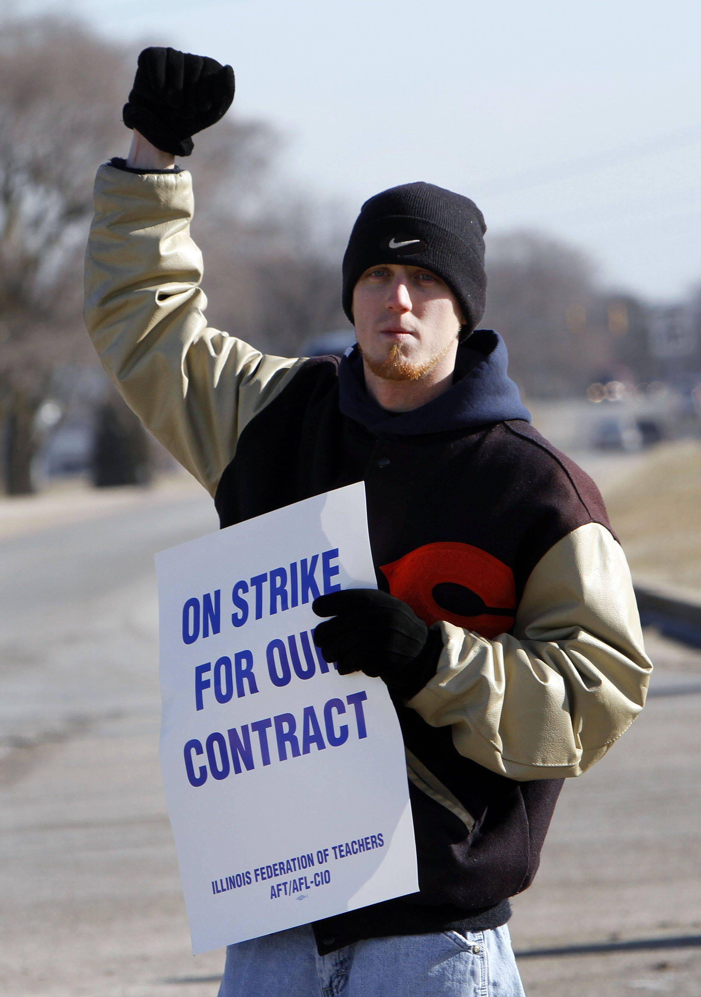 Zion-Benton Township High School social worker Jonathan Mahoney acknowledges honking motorists as employees picket in front of the high school Thursday.