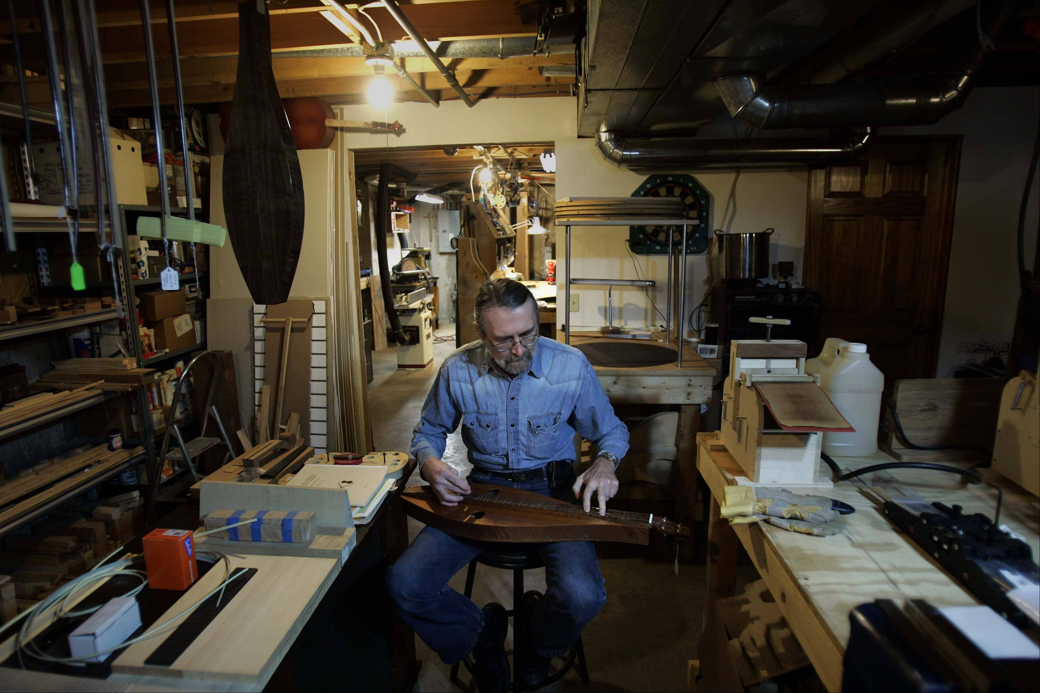 Brunkalla plays one of his handmade dulcimers in his workshop.