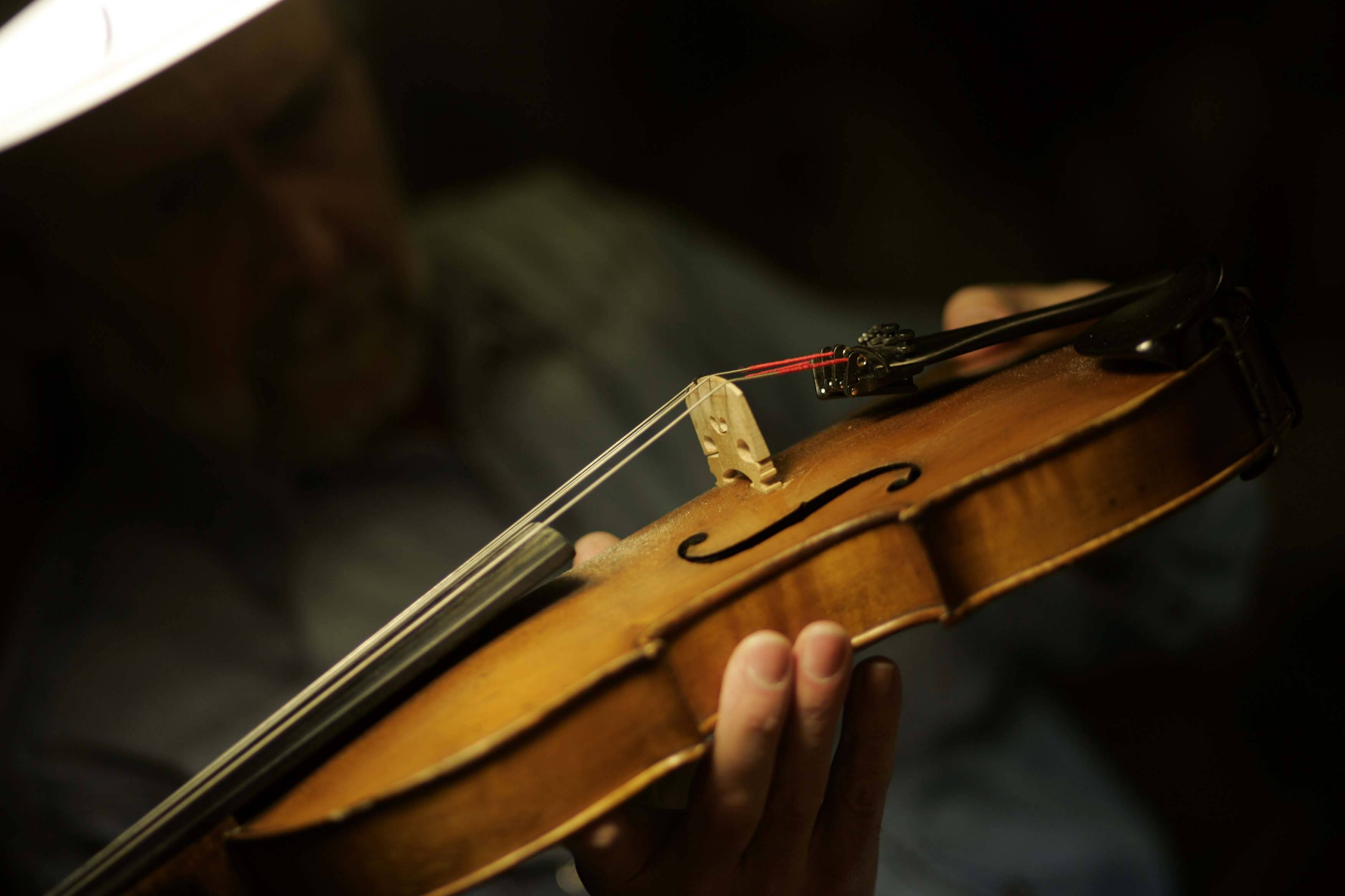 Brunkalla checks to make sure the sound post is in the correct place on a violin that was brought in for repair.