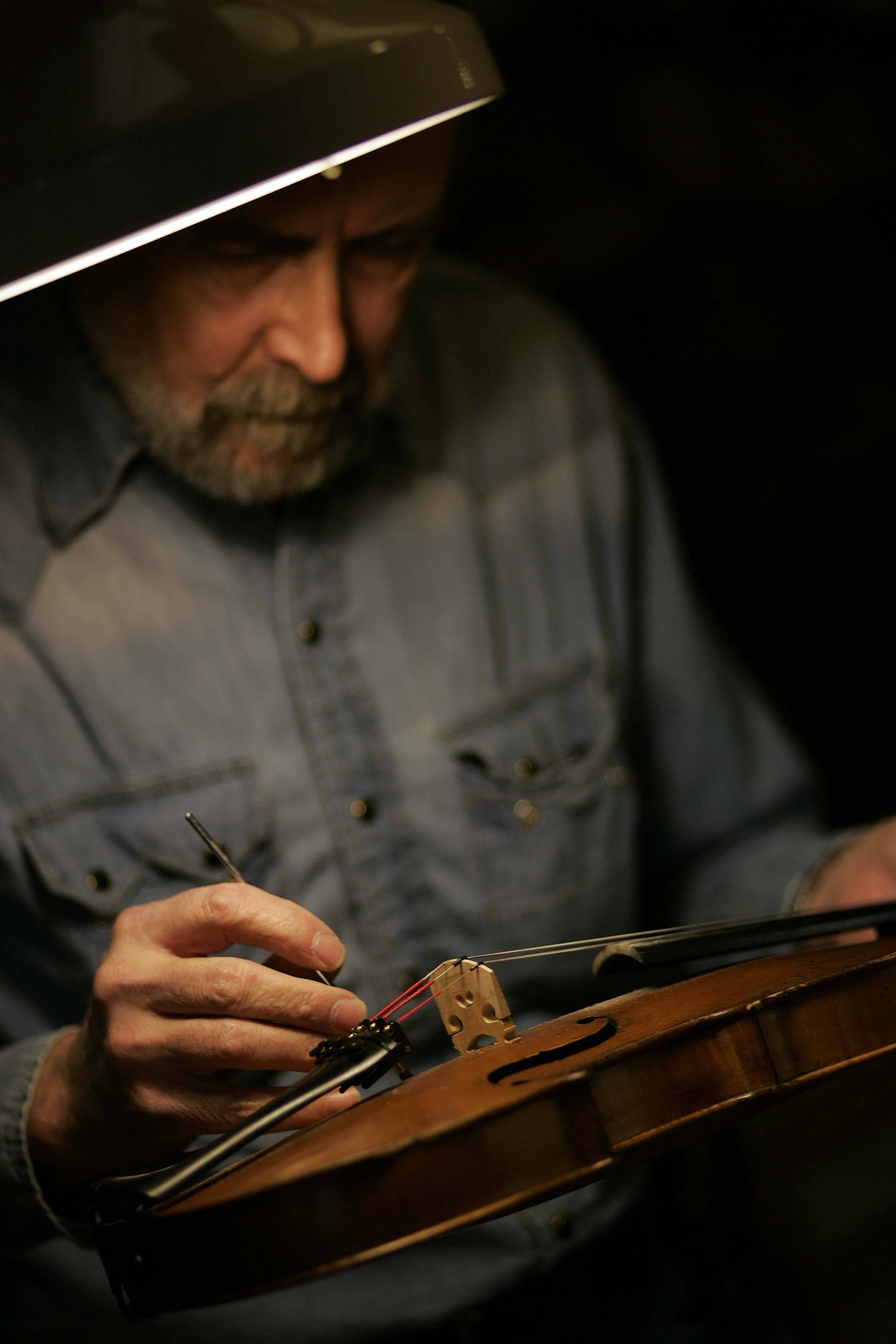 Brunkalla makes adjustments to the sound post of a violin that was brought in for repair.