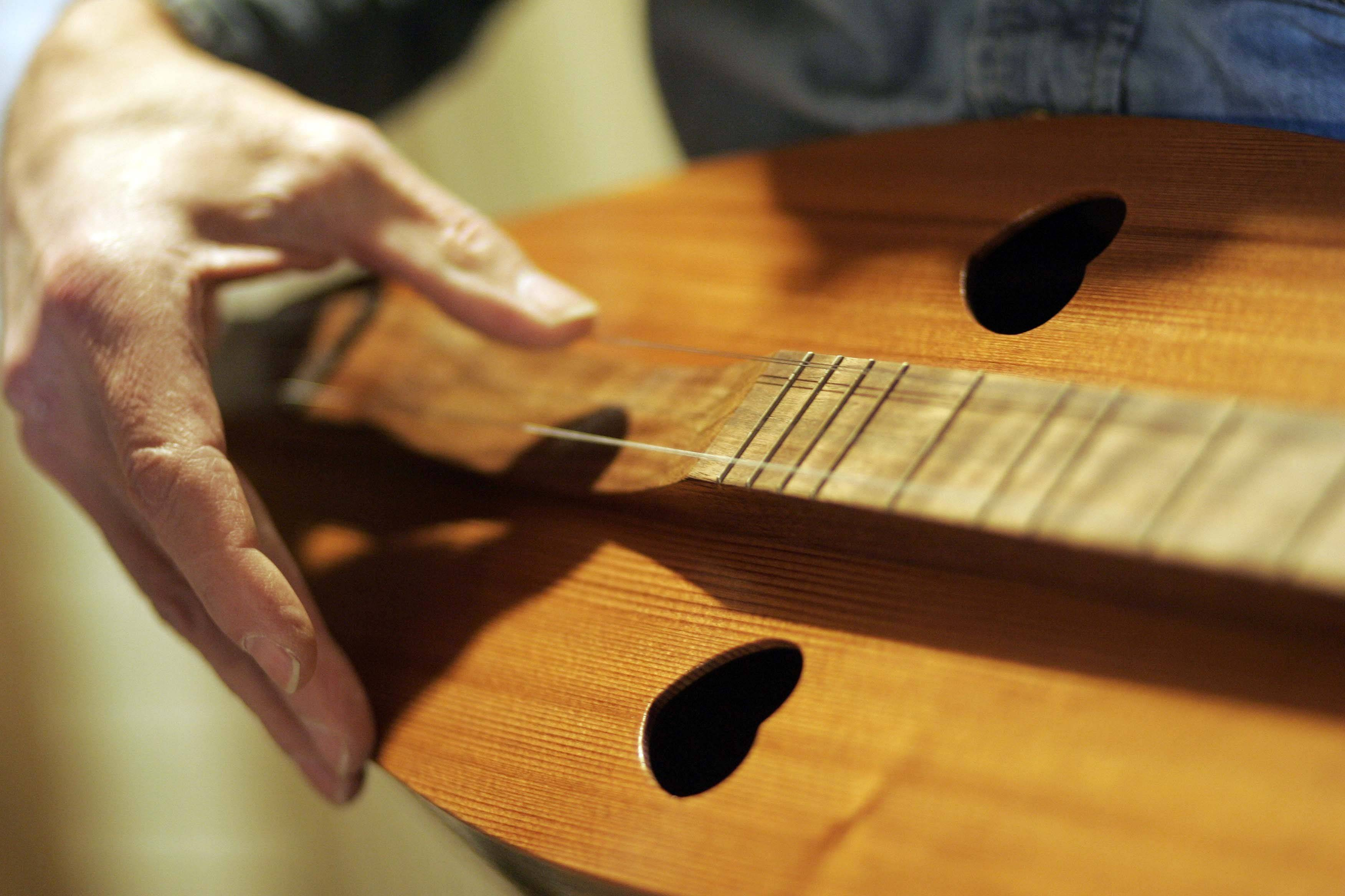Brunkalla plays one of his handmade dulcimers in his Marengo workshop.