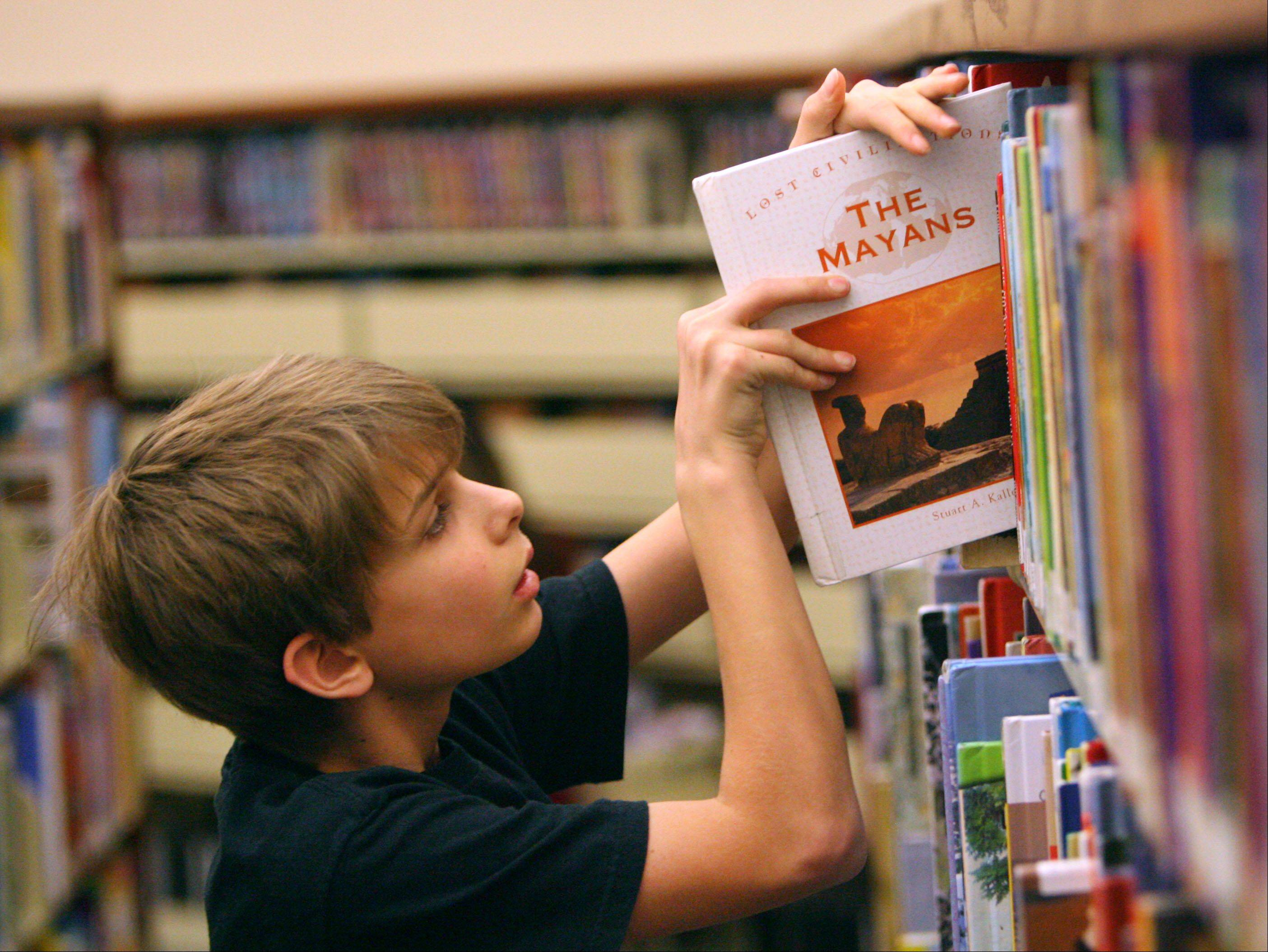Jared Burgess, 12, of Lindenhurst looks for a book at Lake Villa District Library. From Jan. 2-28, the library will donate $1 to the Lake Villa Township Food Pantry (up to $5 per child) for every hour a child reads.