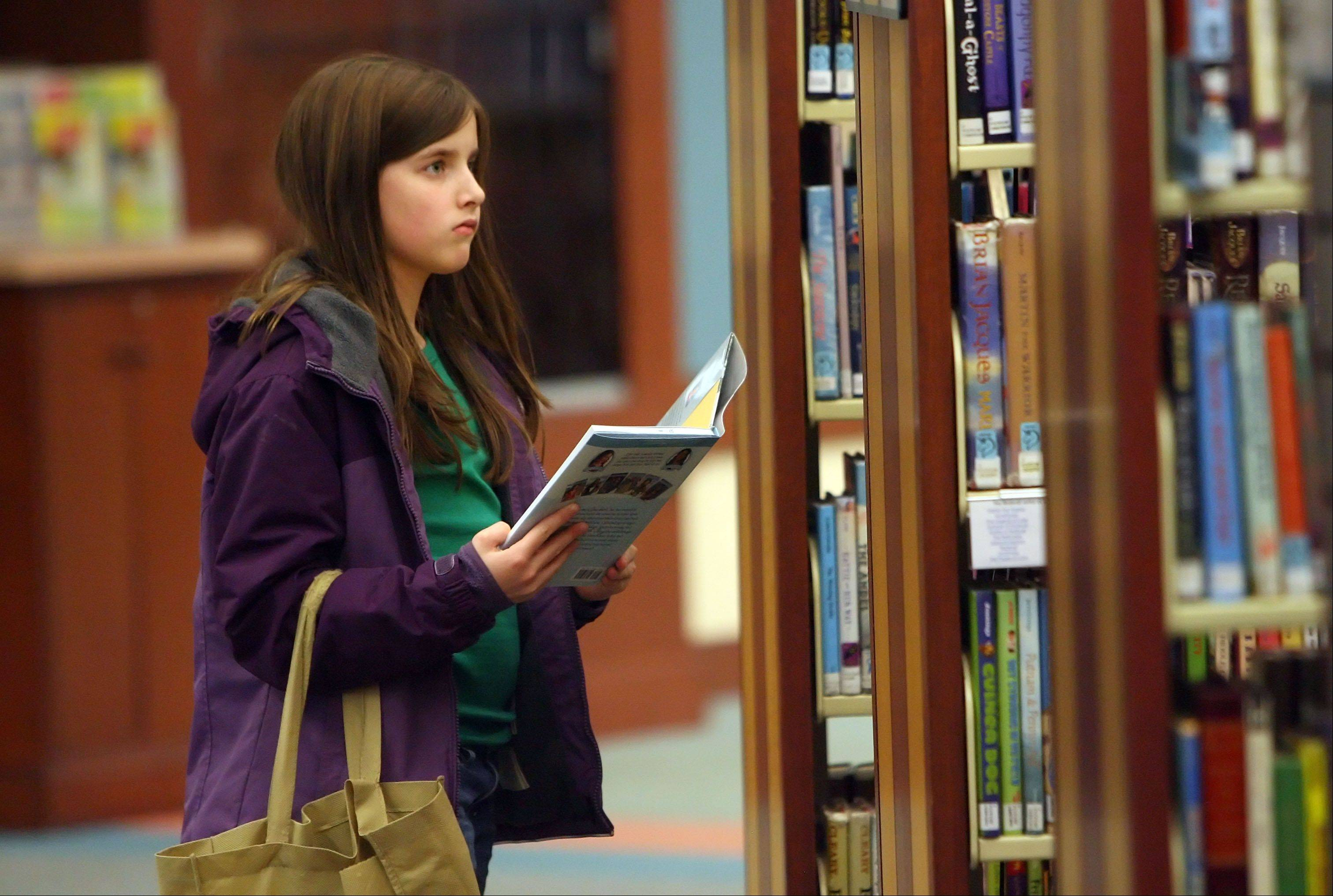 Olivia Caggiano, 9, of Lake Villa looks through books in the children's section at Lake Villa District Library.