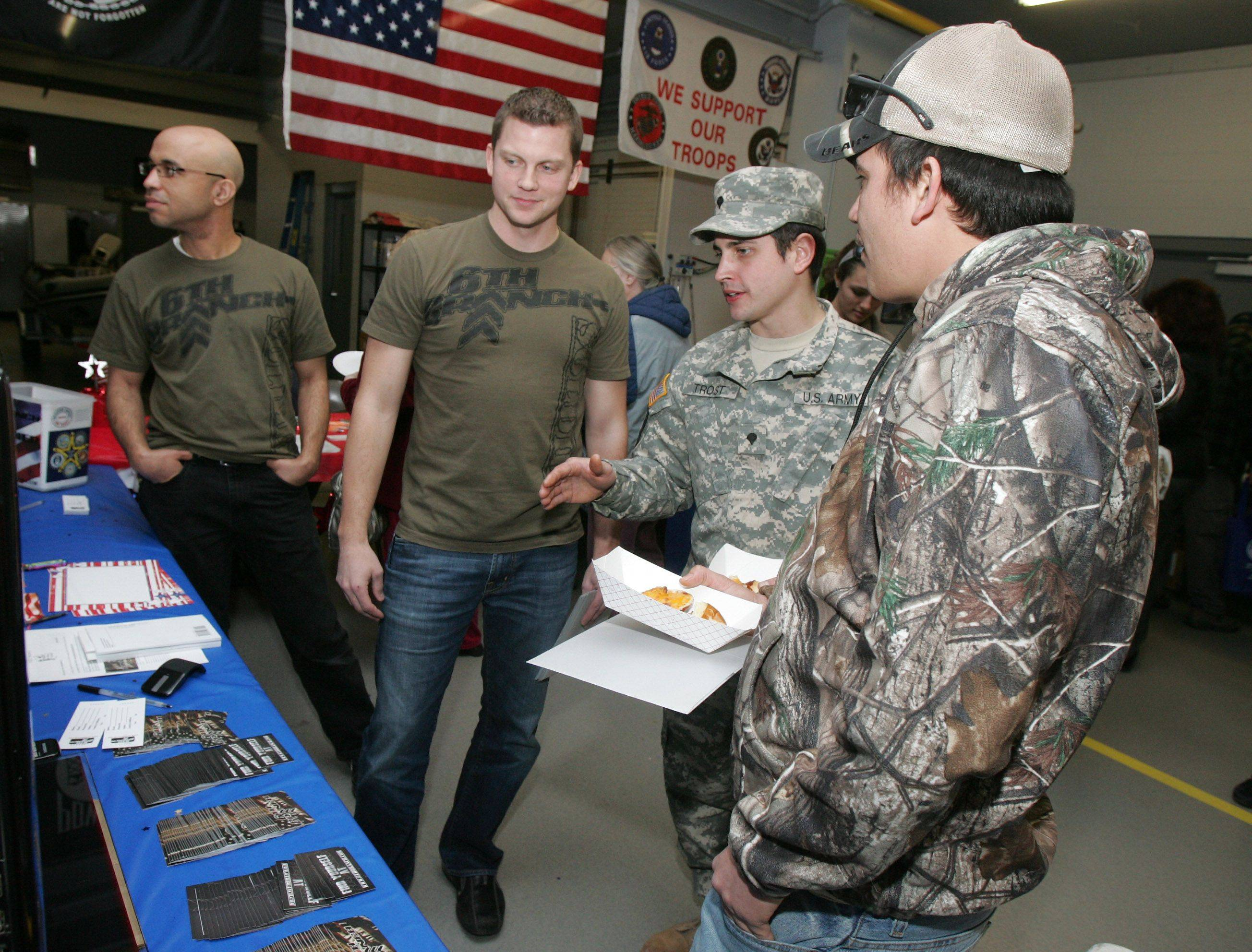 "Army Specialist Adam Trost of Lake Villa, center, talks with Ben Thompson, left, and Raul Gutierrez about 6th Branch during the Oasis Grayslake Youth Center's ""Welcome Home"" event Sunday for military personnel who served in an overseas war. 6th Branch is a Lake County organizations that provides care packages for overseas troops."