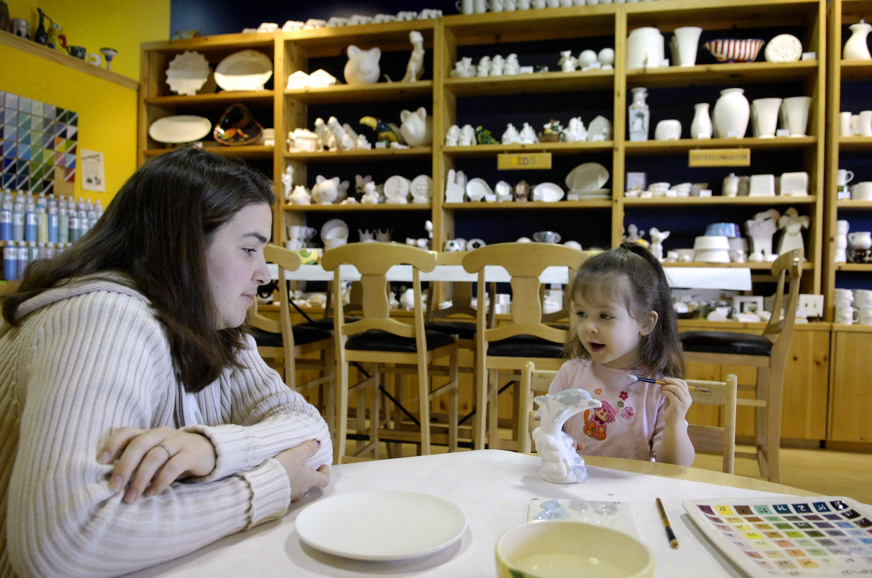 Roseanna Kocan of North Aurora watches as her 2-year-old daughter Hannah paints a ceramic dolphin at Color Me Mine in the Geneva Commons. The studio will offer discounts on Saturday evenings to customers wearing pajamas.