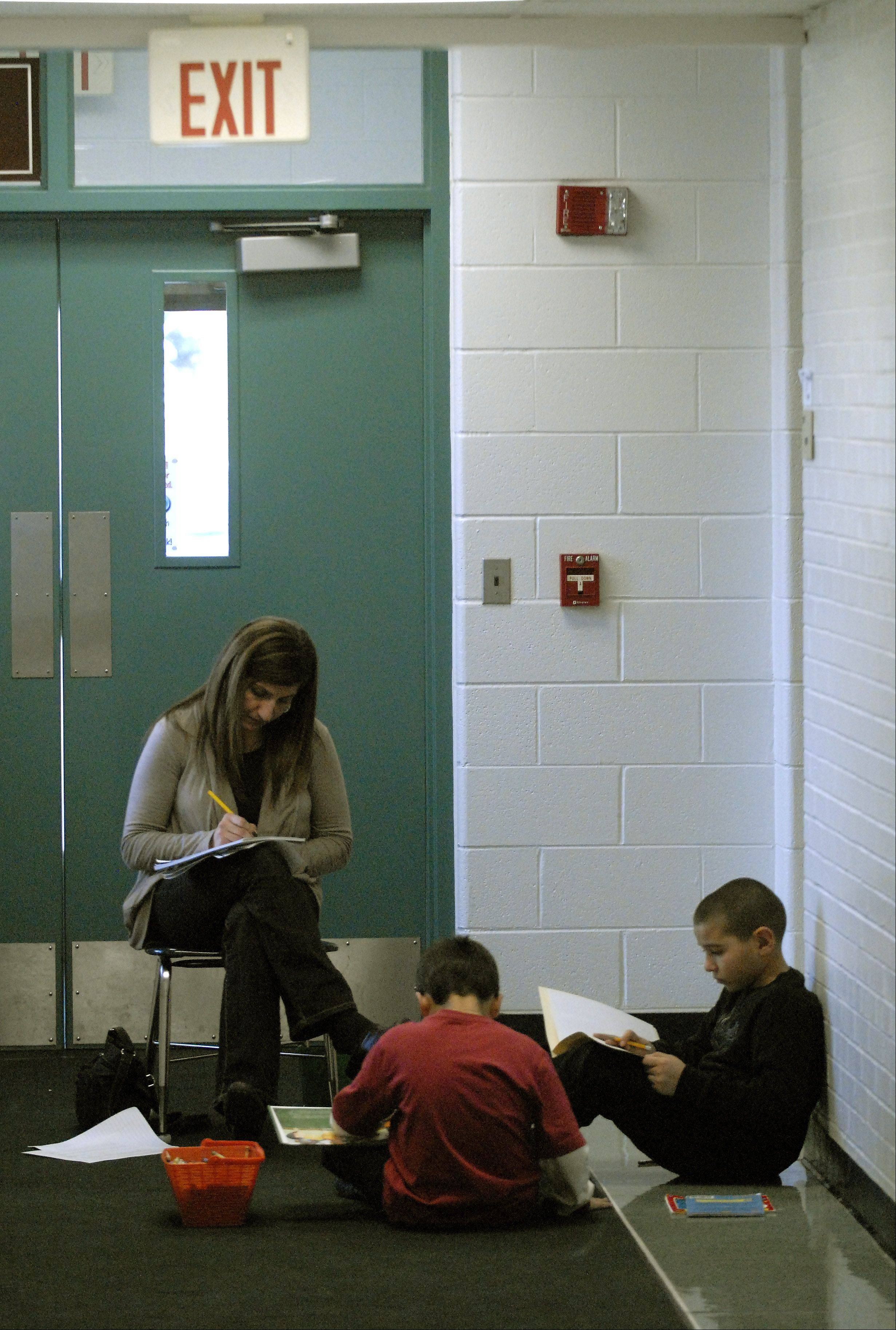 A teacher works with students in the hallway at Robert Frost Elementary School in Mount Prospect. Elk Grove Township Elementary District 59 will conduct three public forums to address overcrowding at the school.
