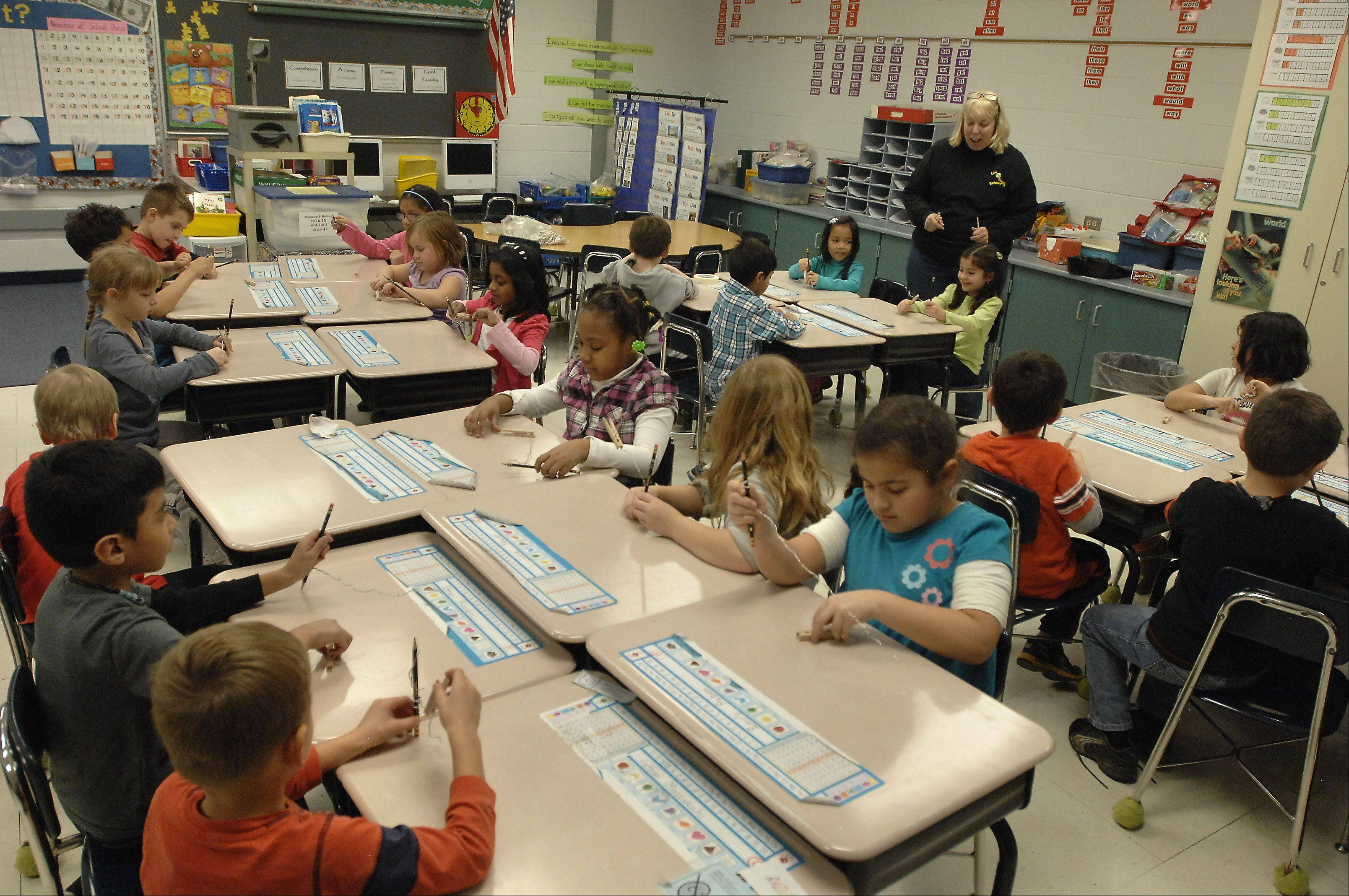 Pam Schakowsky teaches a science experiment to her first-grade class at Robert Frost Elementary School in Mount Prospect. Elk Grove Township Elementary District 59 will conduct three public forums this month to address overcrowding at the school.