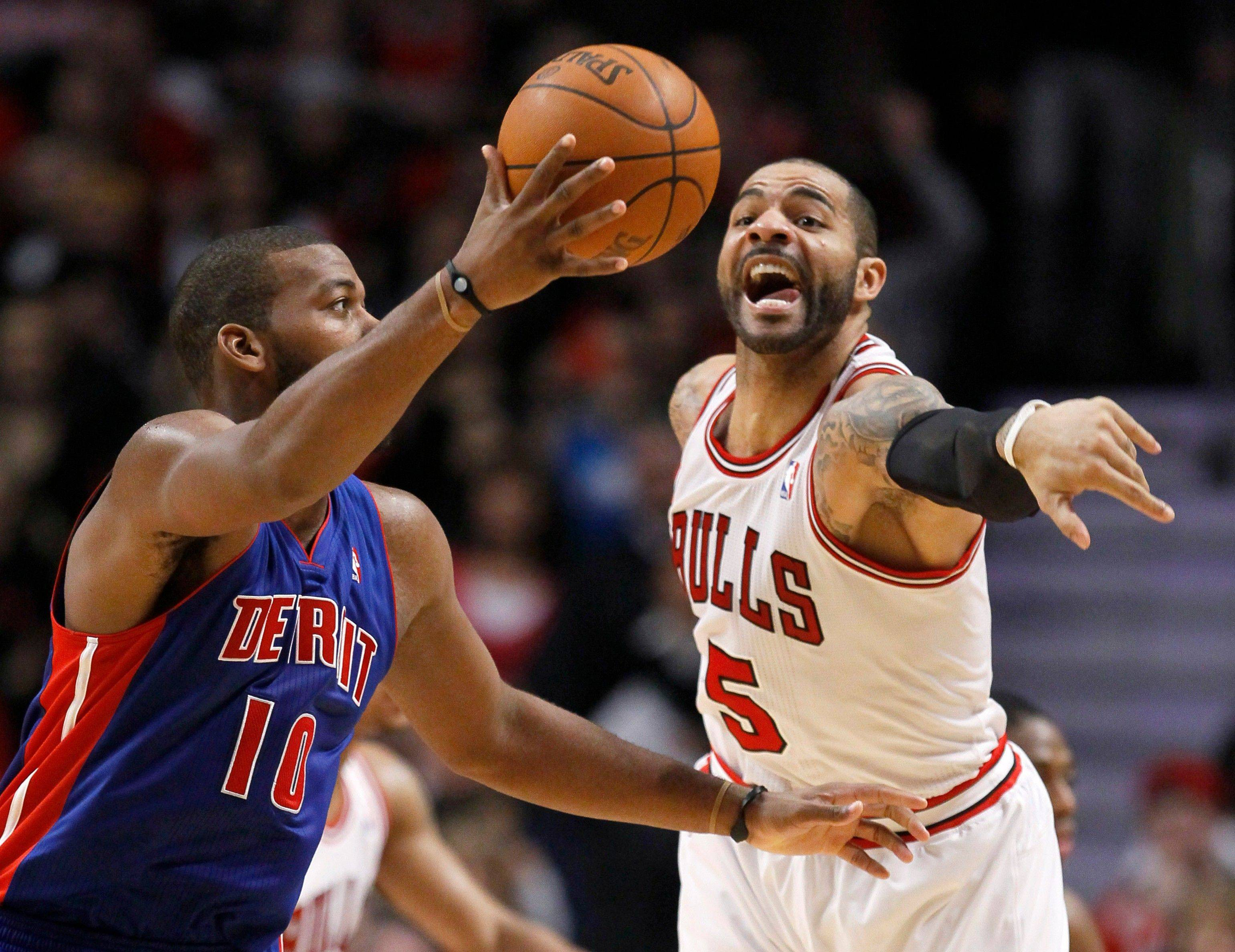 Bulls forward Carlos Boozer tries to knock the ball away from Detroit Pistons center Greg Monroe during the second half Monday night at the United Center. Boozer led all scorers with 23 points in the Bulls' 92-68 win.