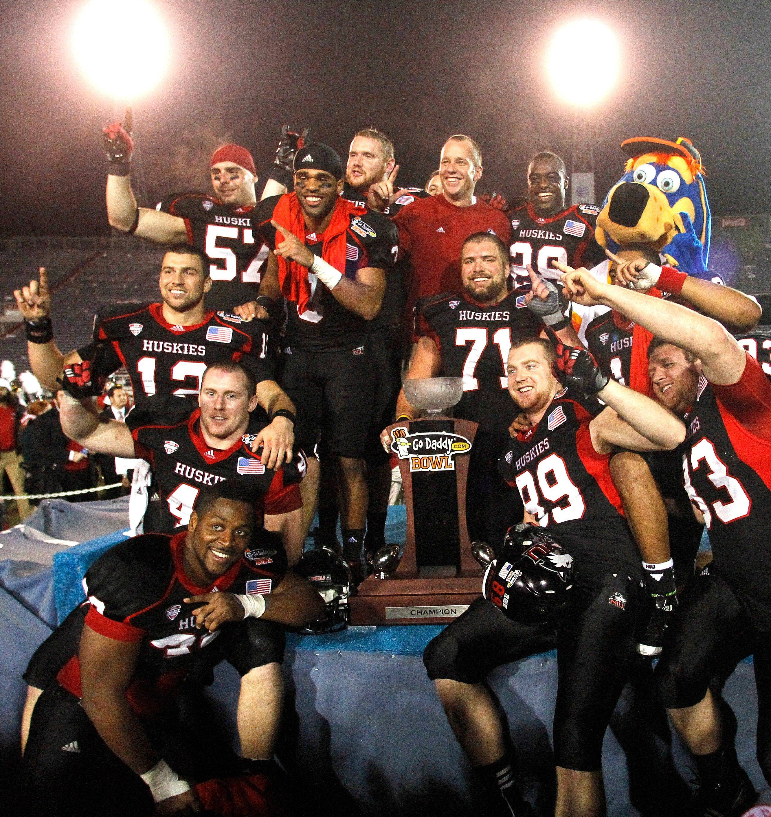 Coach Dave Doeren is surrounded by his Northern Illinois players as they celebrate their 38-20 victory over Arkansas State in the GoDaddy.com Bowl on Sunday night.
