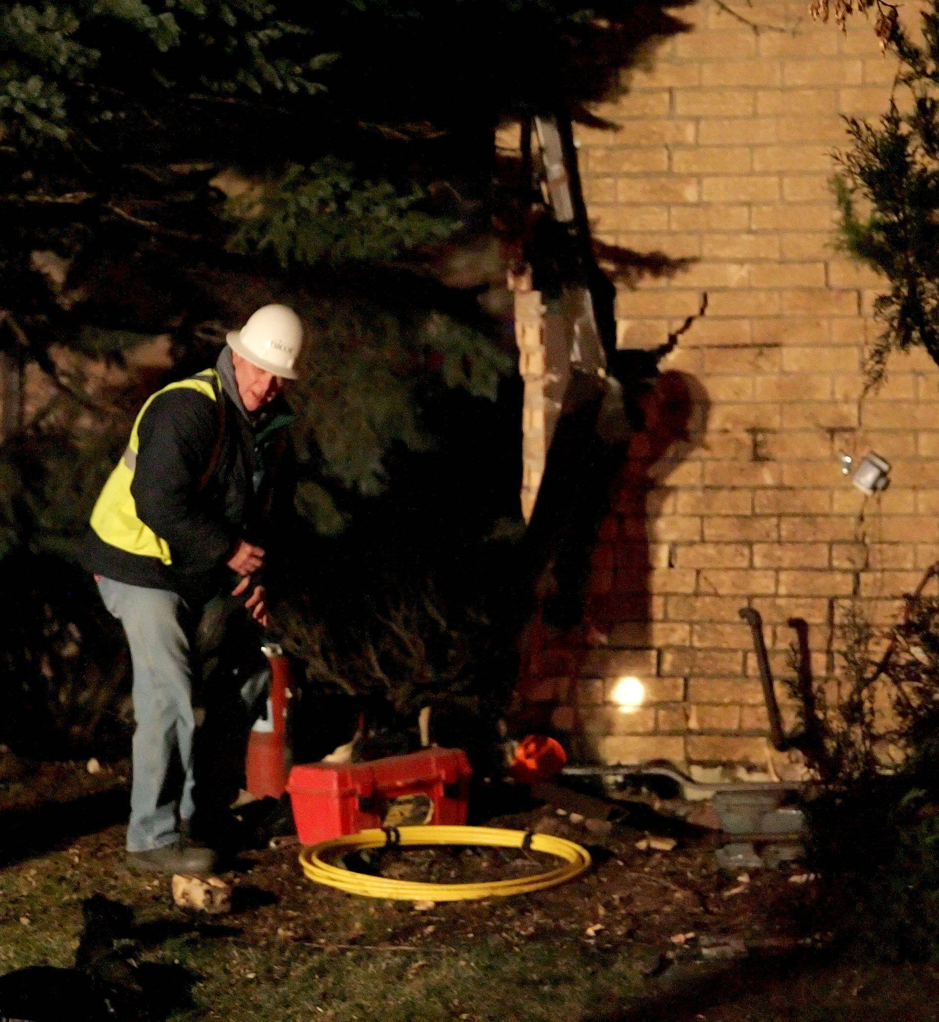 Crews investigate damage done to a house after a one-car accident at the intersection of Naperville Road and Farnham Lane in Wheaton on Tuesday.