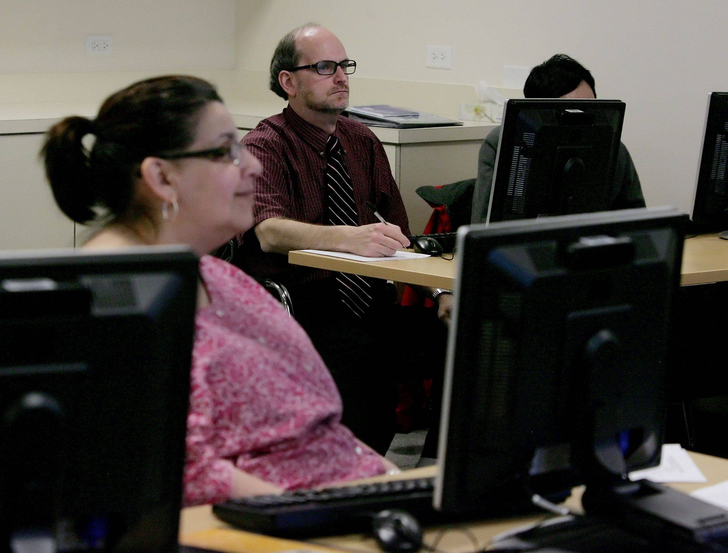 Vernon Hills resident Ellen Peckler, foreground, and Libertyville's Michael Page listen to the instructor during a jobs workshop Tuesday at the Cook Park Library in Libertyville. Libraries have become resources for unemployed people during the nation's economic struggles.