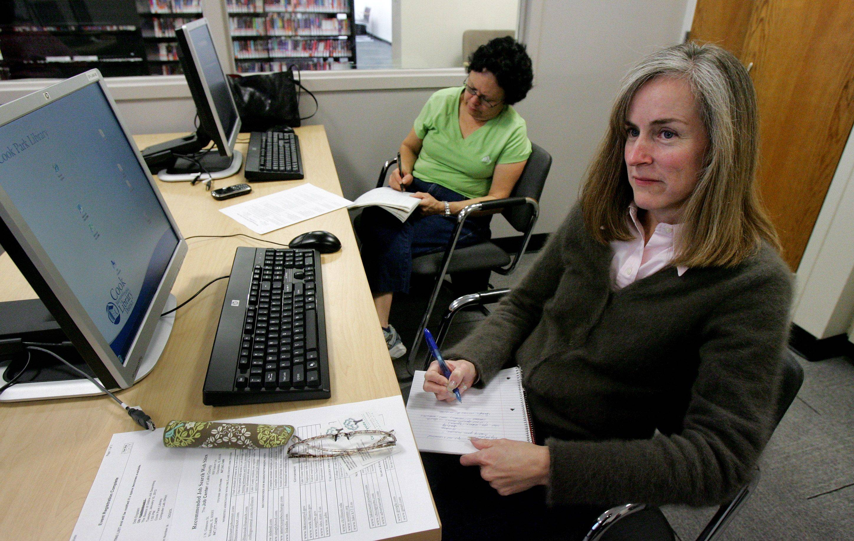 Debbie Engdahl of Mundelein, right, and Ethel Pickar of Libertyville take notes during a jobs workshop Tuesday at the Cook Park Library in Libertyville.