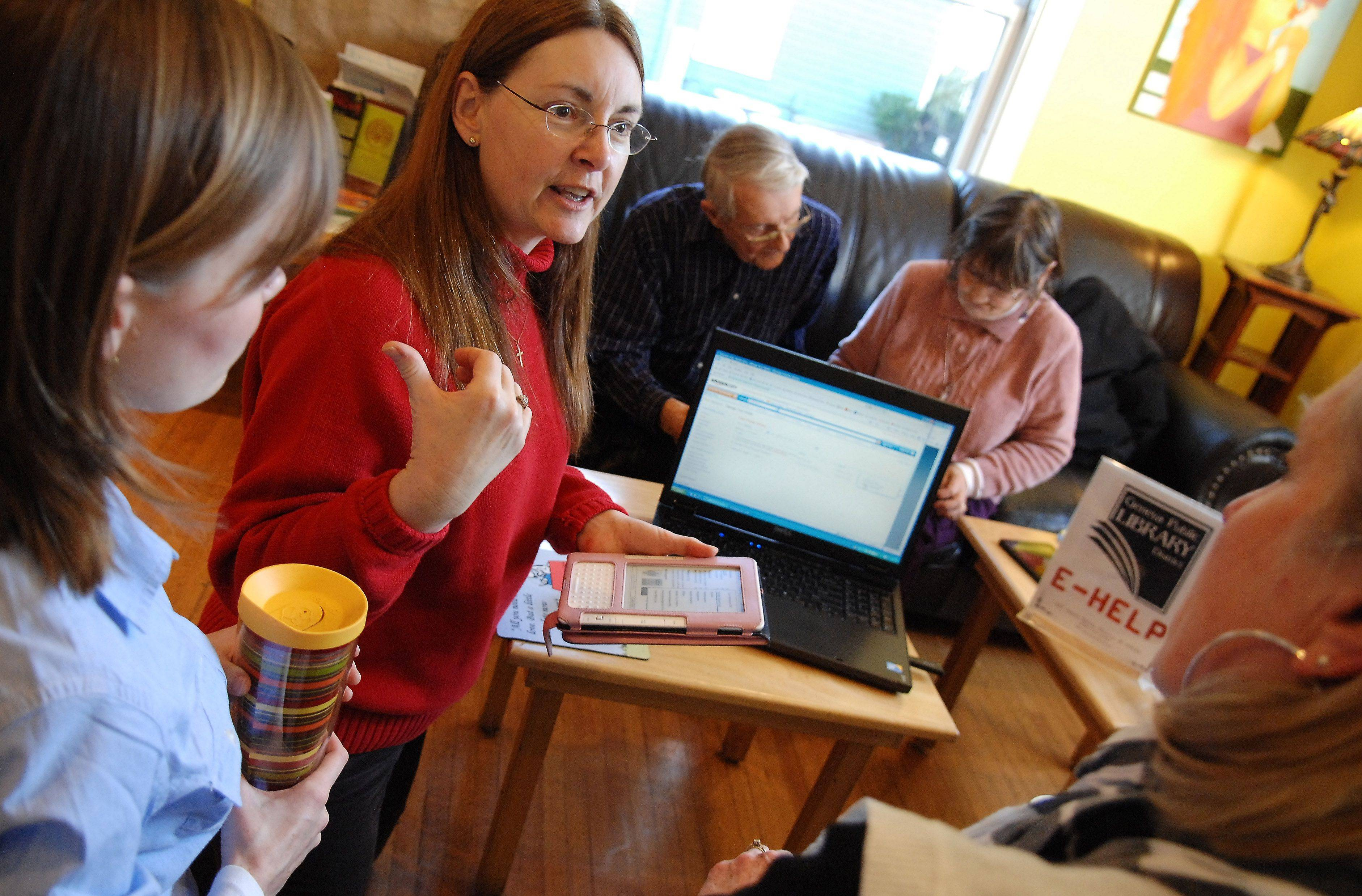 Geneva Library reference assistant Christine Dalphy helps a group learn how to use their various e-readers to check out books from the library Monday afternoon at Graham's 318 in Geneva.