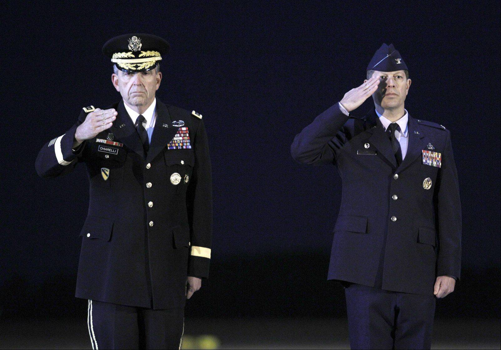Vice Chief of Staff Army Gen. Peter W. Chiarelli, left, and Air Force Col. Thomas Joyce salute Sunday as the remains of Army Staff Sgt. Jonathan M. Metzger of Indianapolis, Army Spc. Brian J. Leonhardt of Merrillville, Ind., Army Spc. Christopher Patterson of North Aurora and Army Spc. Robert J. Tauteris Jr. of Hamlet, Ind., upon arrival at Dover Air Force Base in Delaware. The men were killed in Afghanistan last week.