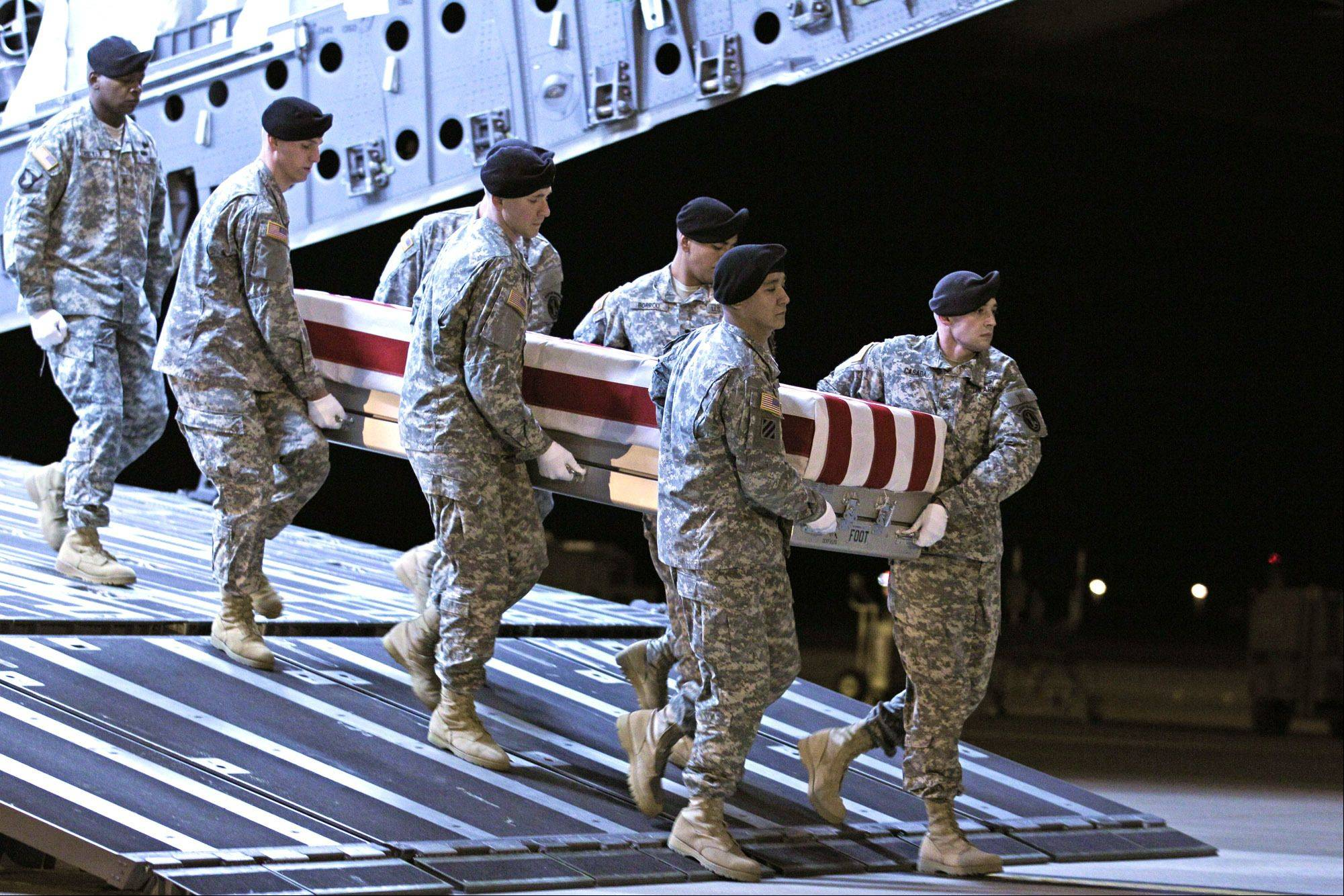 An Army carry team moves the transfer case containing the remains of Spc. Christopher Patterson of North Aurora upon arrival at Dover Air Force Base Sunday. Patterson was serving with the 713th Engineer Company, Indiana National Guard, in Afghanistan. Patterson's funeral is Jan. 20 in Batavia.