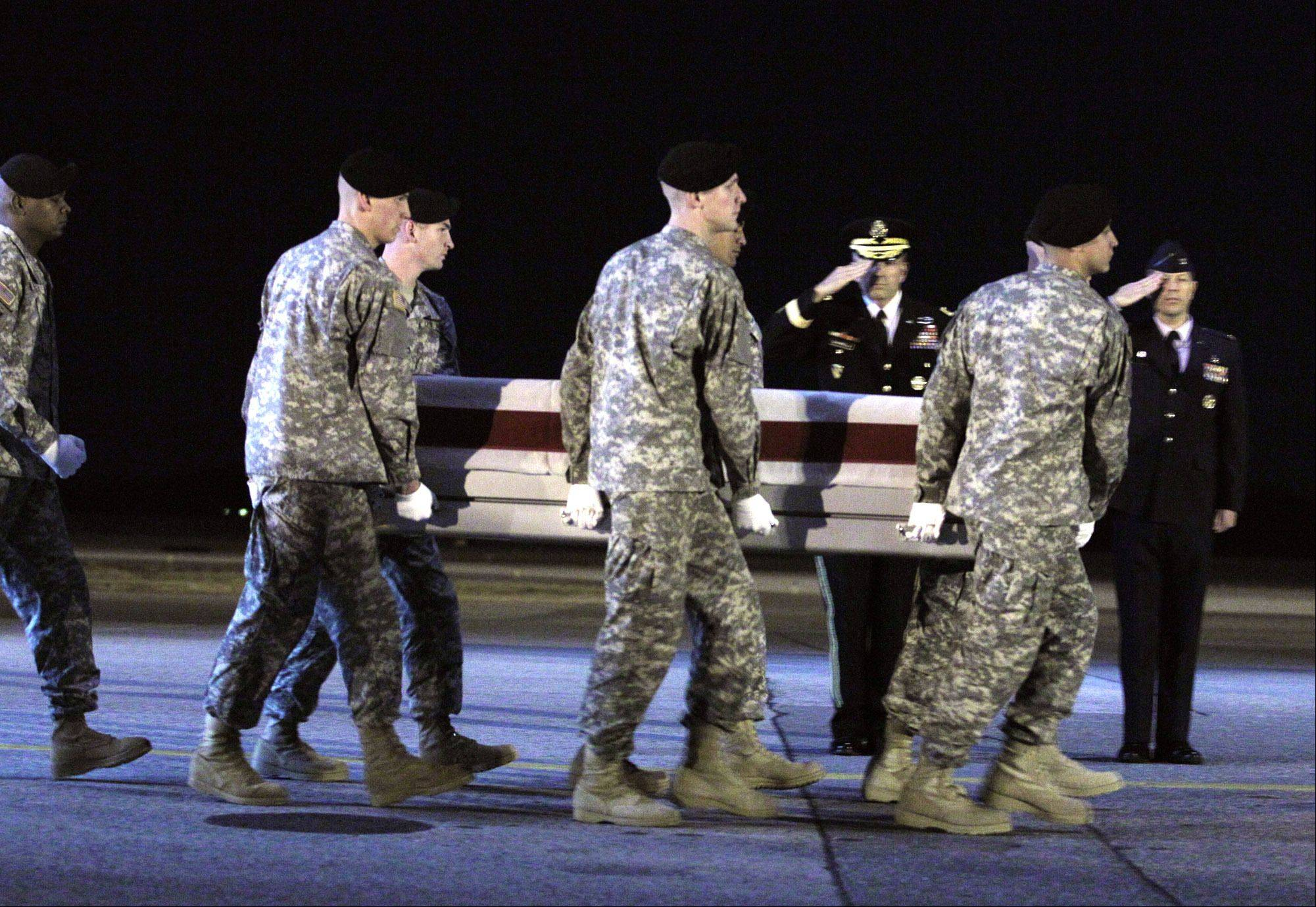 An Army carry team moves the transfer case containing the remains of Army Spc. Christopher Patterson of North Aurora upon arrival at Dover Air Force Base Sunday.