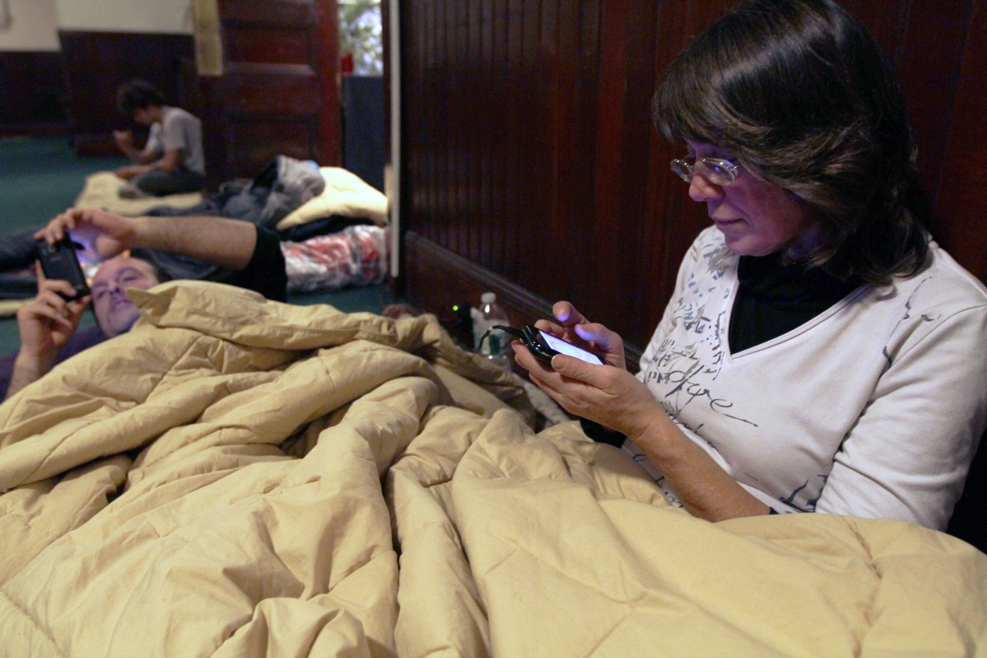 Donna Marinelli, of New Britain, Conn., foreground, and her cousin David Monarca, use their phones as they spend the night in a church space being funded by Occupy Wall Street for Occupy Wall Street protesters at the West Park Presbyterian Church in New York, Wednesday Jan. 11, 2012. The refugees from Manhattanís Zuccotti Park had found their way to the cavernous Presbyterian church, hoping to stay for a few nights, maybe longer.