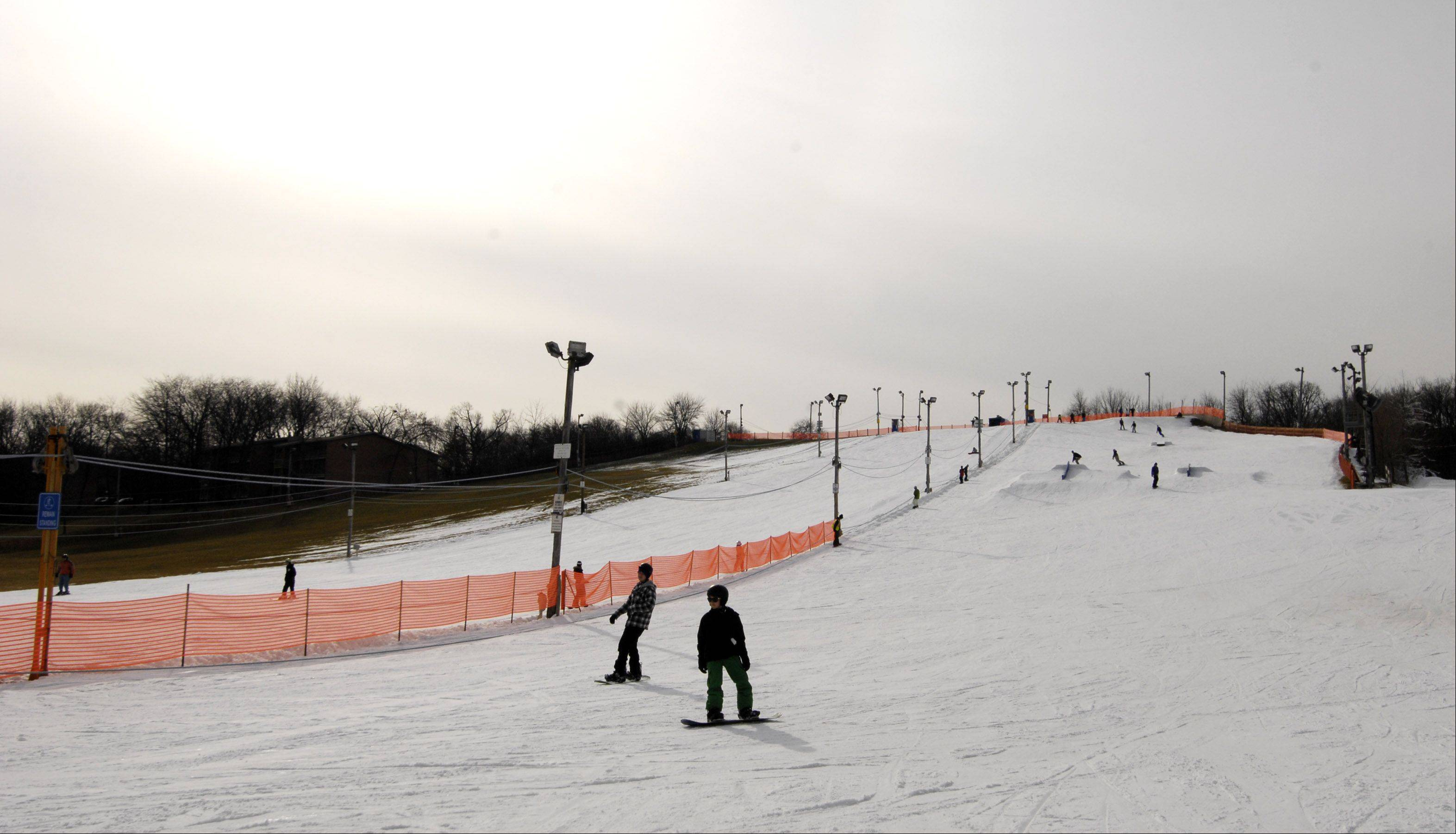 Skiers and snowboarders take to the slopes at Four Lakes Alpine Snowsports in Lisle even with the lack of natural snow. But they're encountering fewer people on the slopes.