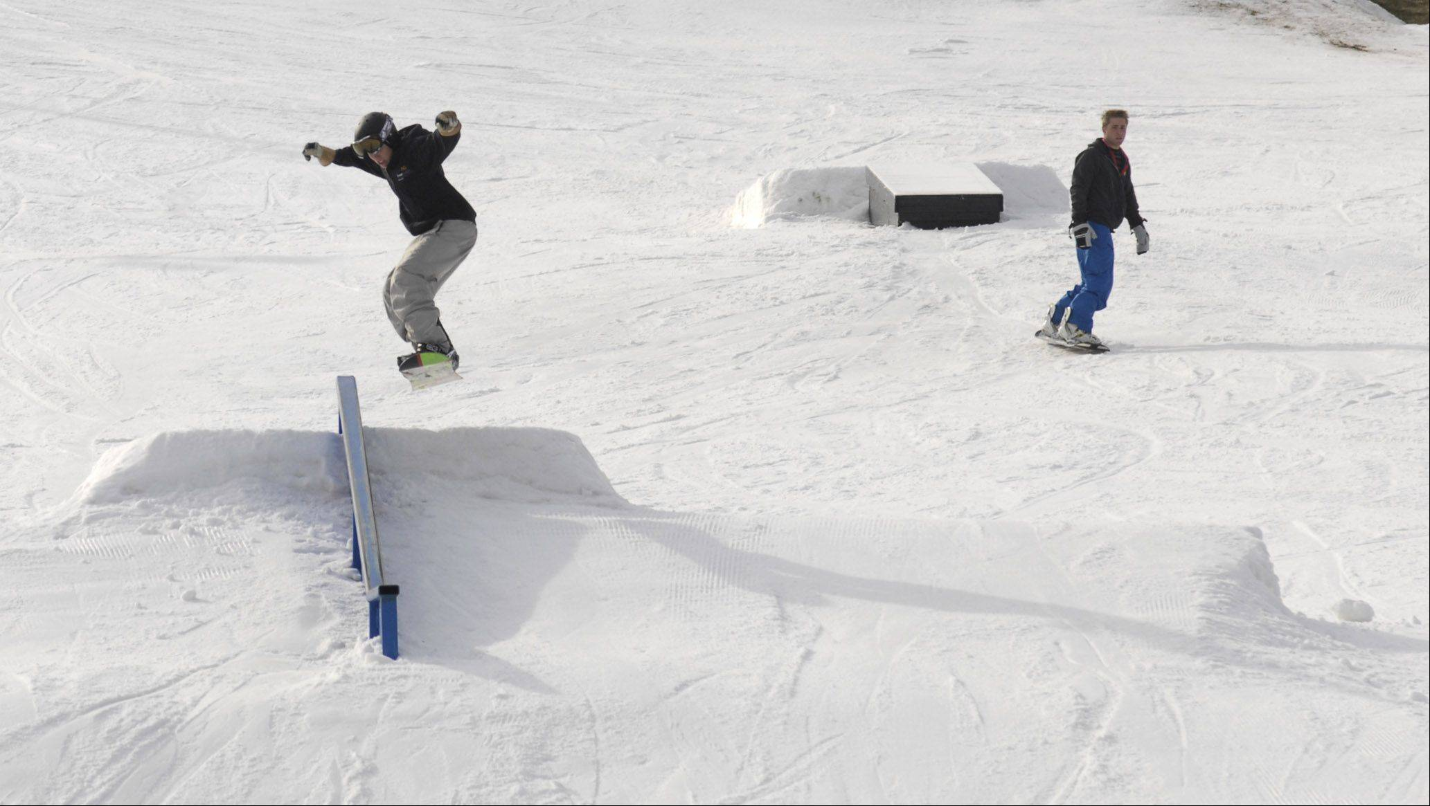 Snowboarders take to the slopes at the Four Lakes Alpine Snowsports in Lisle even with the lack of natural snow.