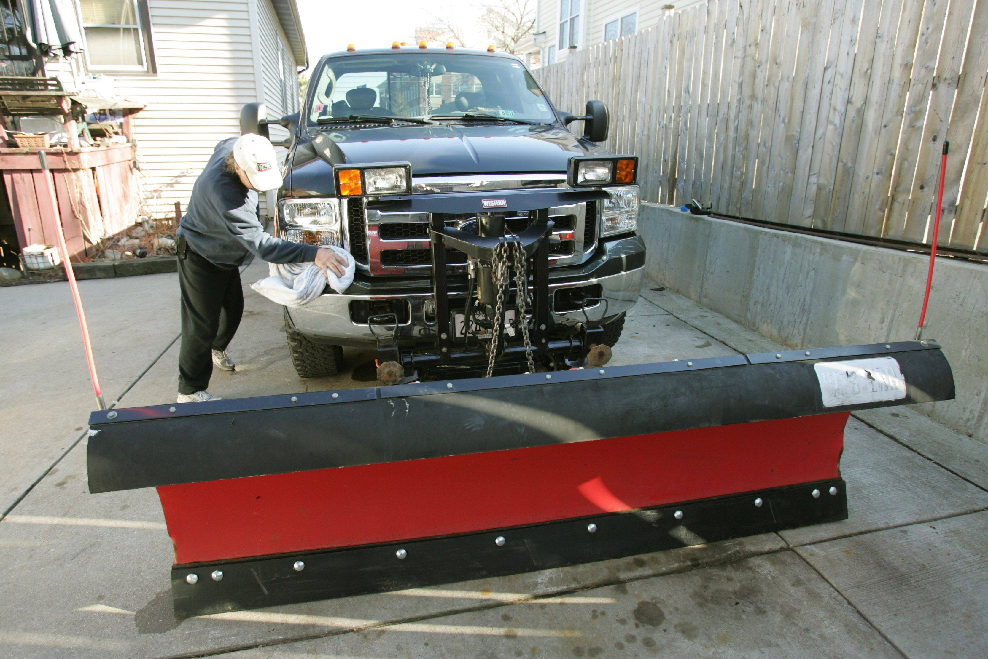 Cold weather-dependent businessman Bob Sadler of Glen Ellyn can't wait to rejuvenate his snow removal business, which has ailed due to warm winter weather. Above, Sadler polishes his plow.