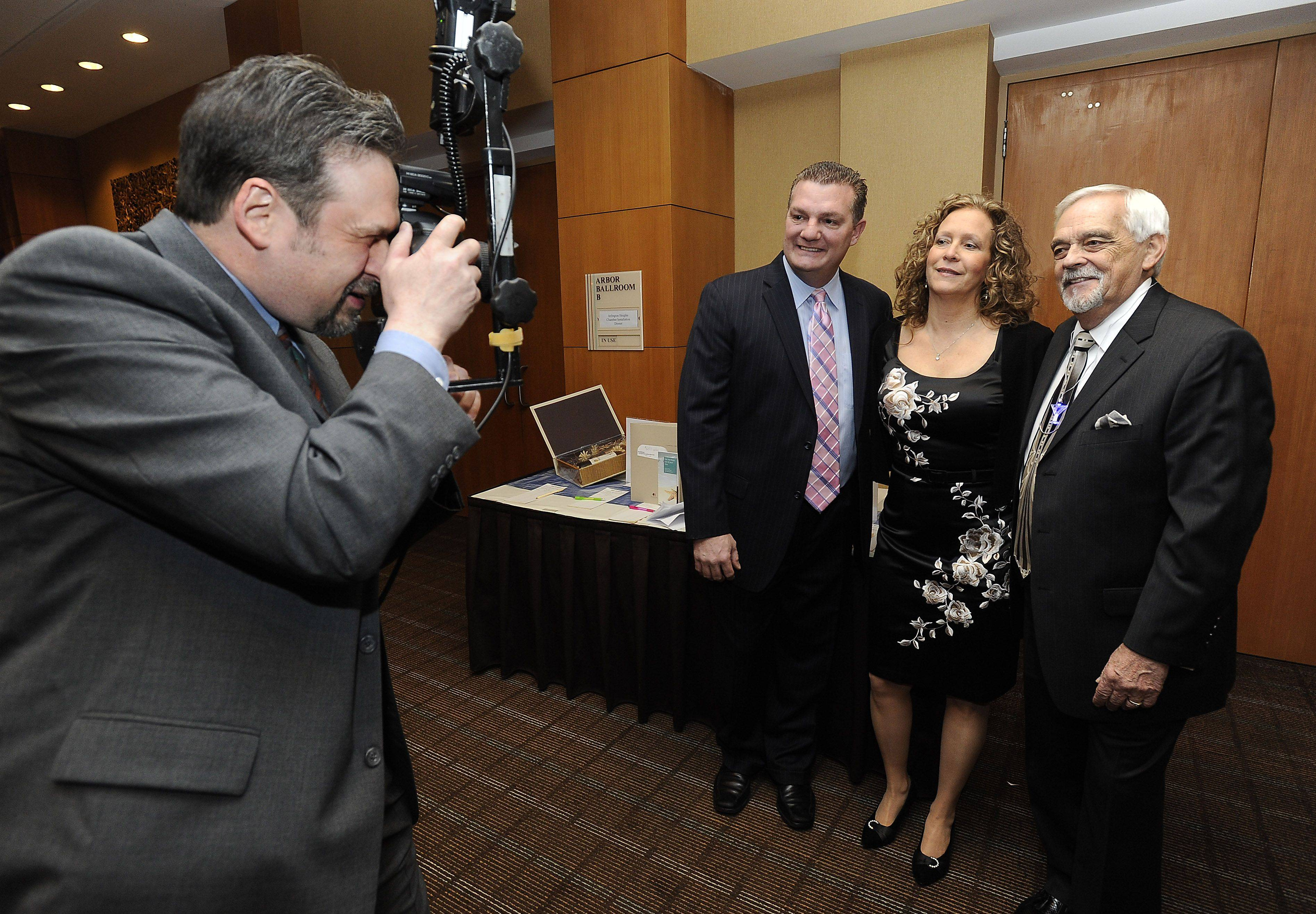 Photographer Steve Sampson shoots a group picture of past Arlington Heights Chamber of Commerce presidents Joe Favia, 2010, and Cindee Manaves, 2011, with the new president, Cliff Higley, at Higley's installation dinner Thursday.