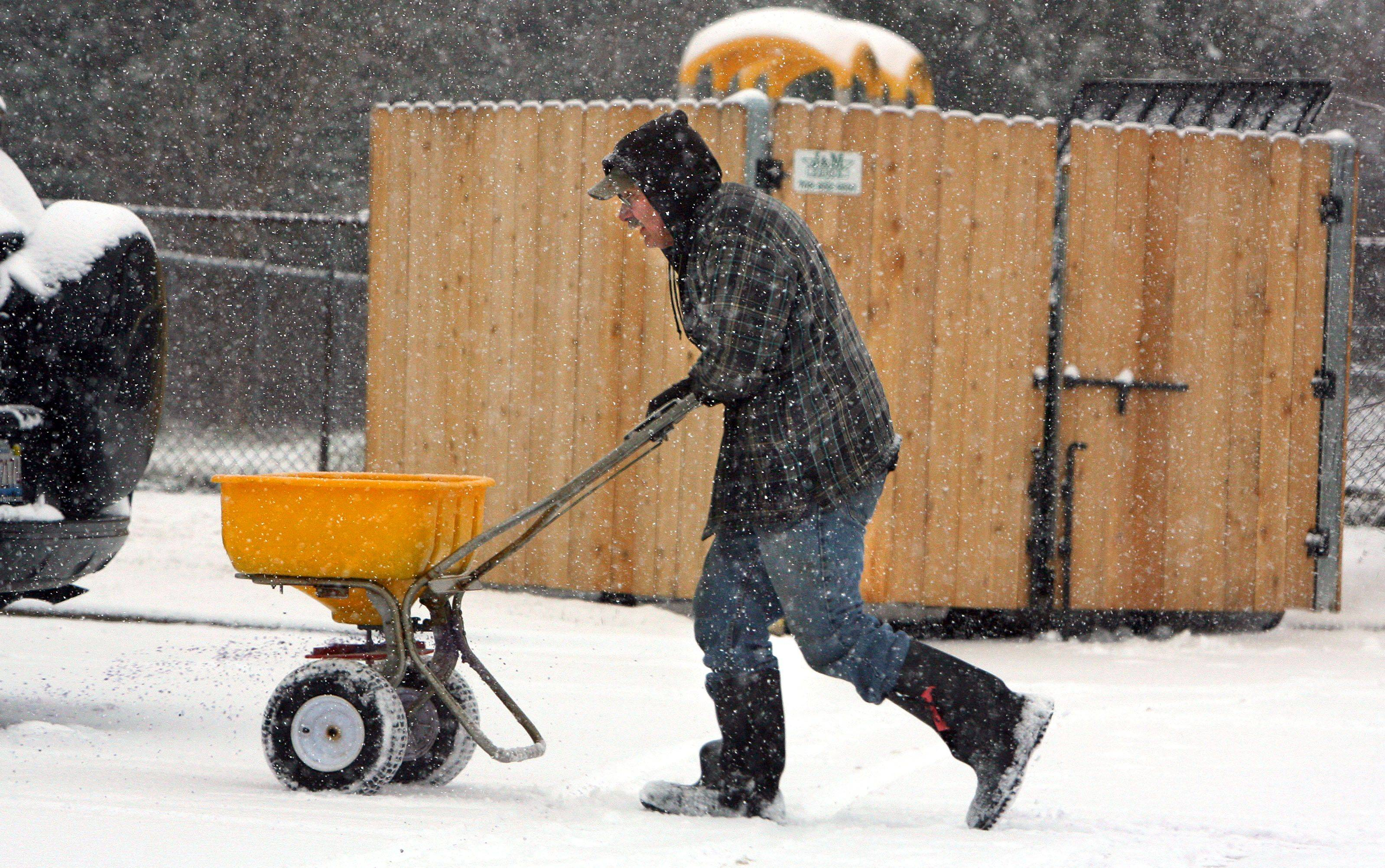 Jim Spiniolas of Carpentersville spreads salt in the parking lot of Kindercare Learning Center in Vernon Hills .