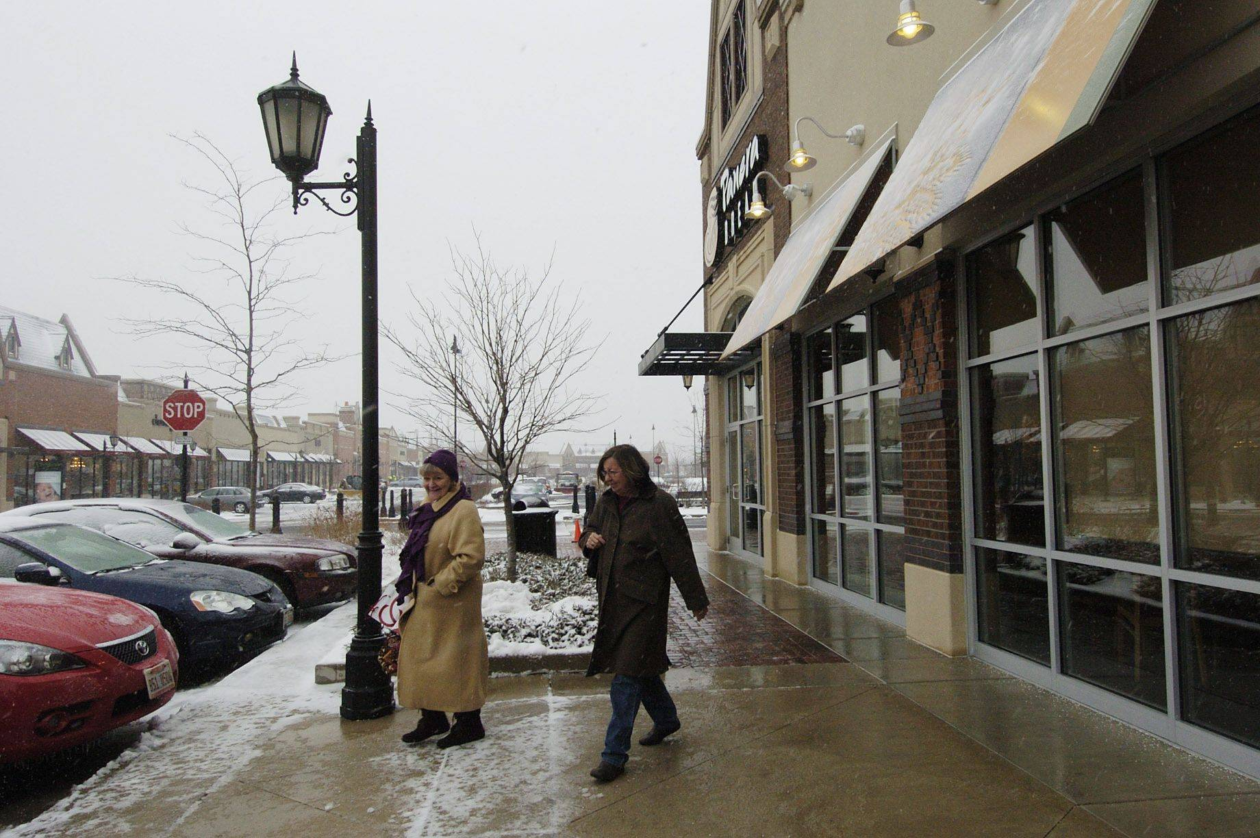 What a difference a day makes at The Arboretum in South Barrington, Ruth Abbate, left, and Bonnie Kearnsey, both of South Barrington, make their way down the sidewalk next to Panera Bread.