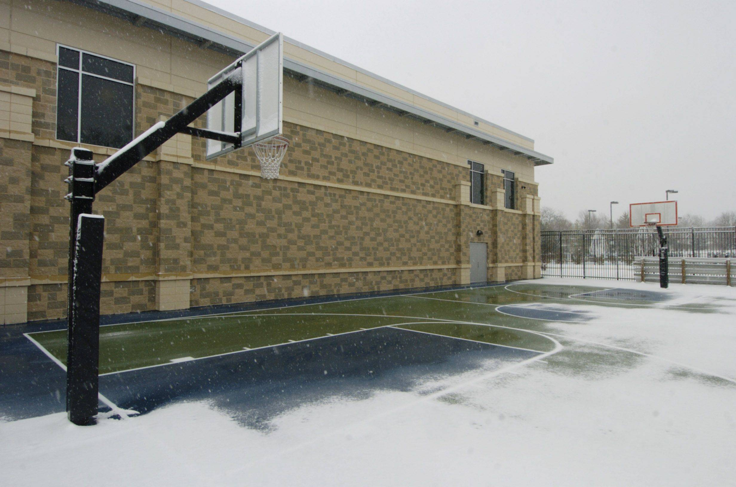 The basketball court at Pioneer Park is partially covered in snow Thursday afternoon. Youths were playing basketball on the court the previous day when the temperature reached 51 degrees.