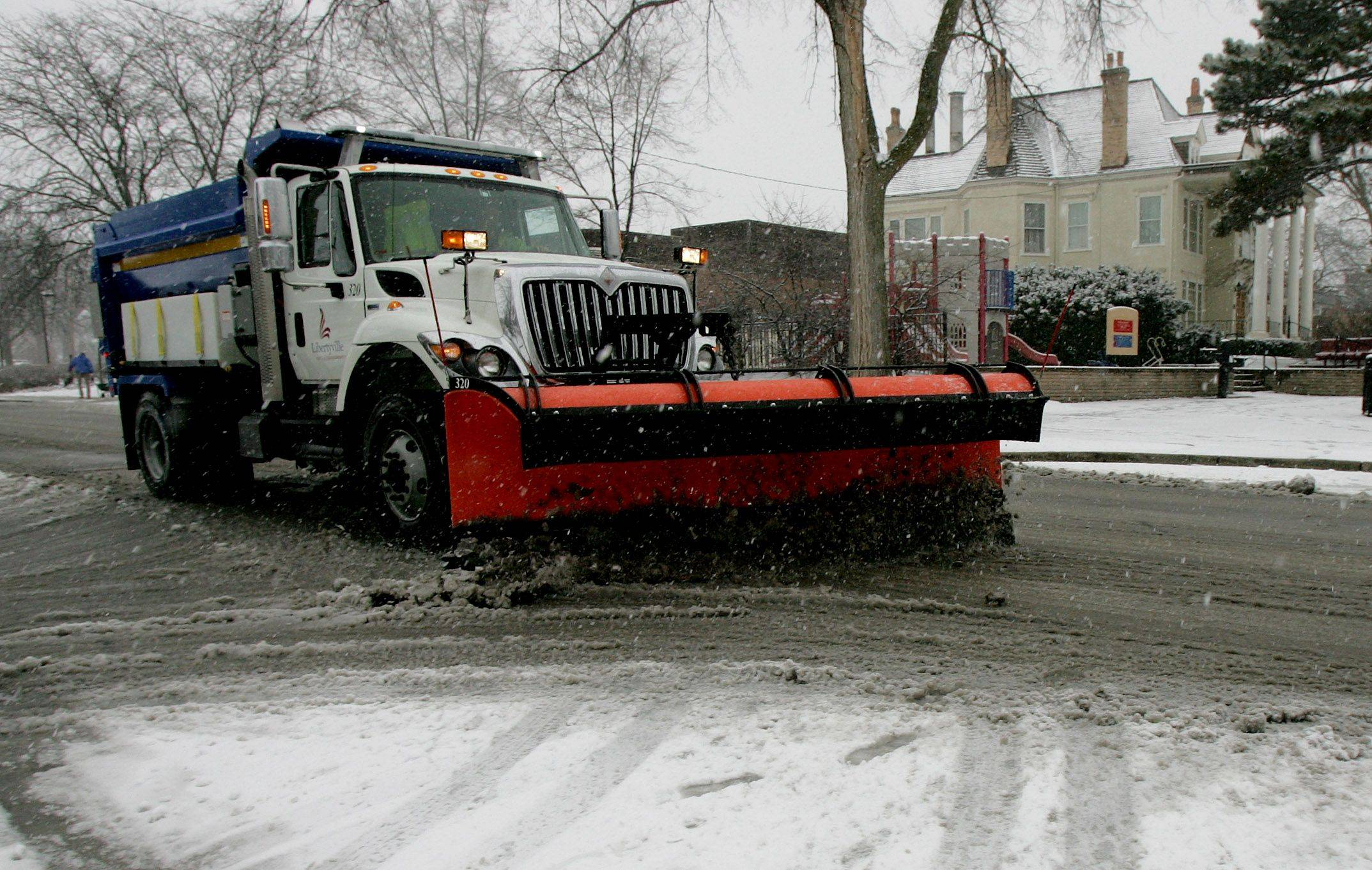 A Libertyville Public Works employee uses a snow plow to clear the roads around Cook Memorial Park.