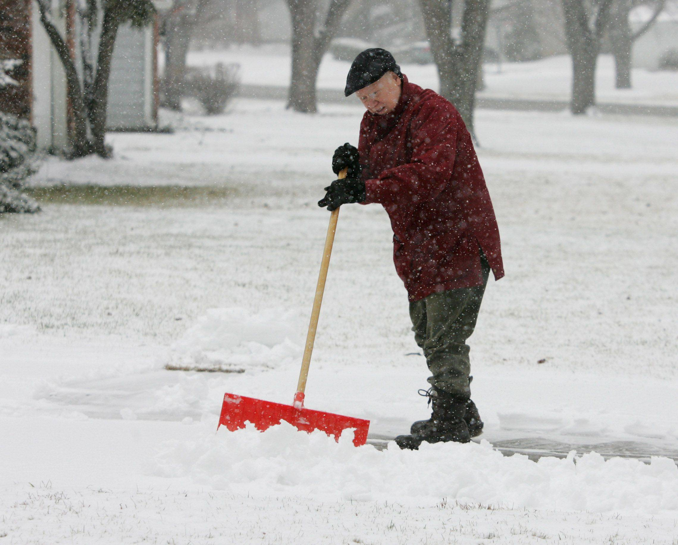 Jim Anderson clears the driveway of a neighbor along Fourth Street in Libertyville on Thursday.
