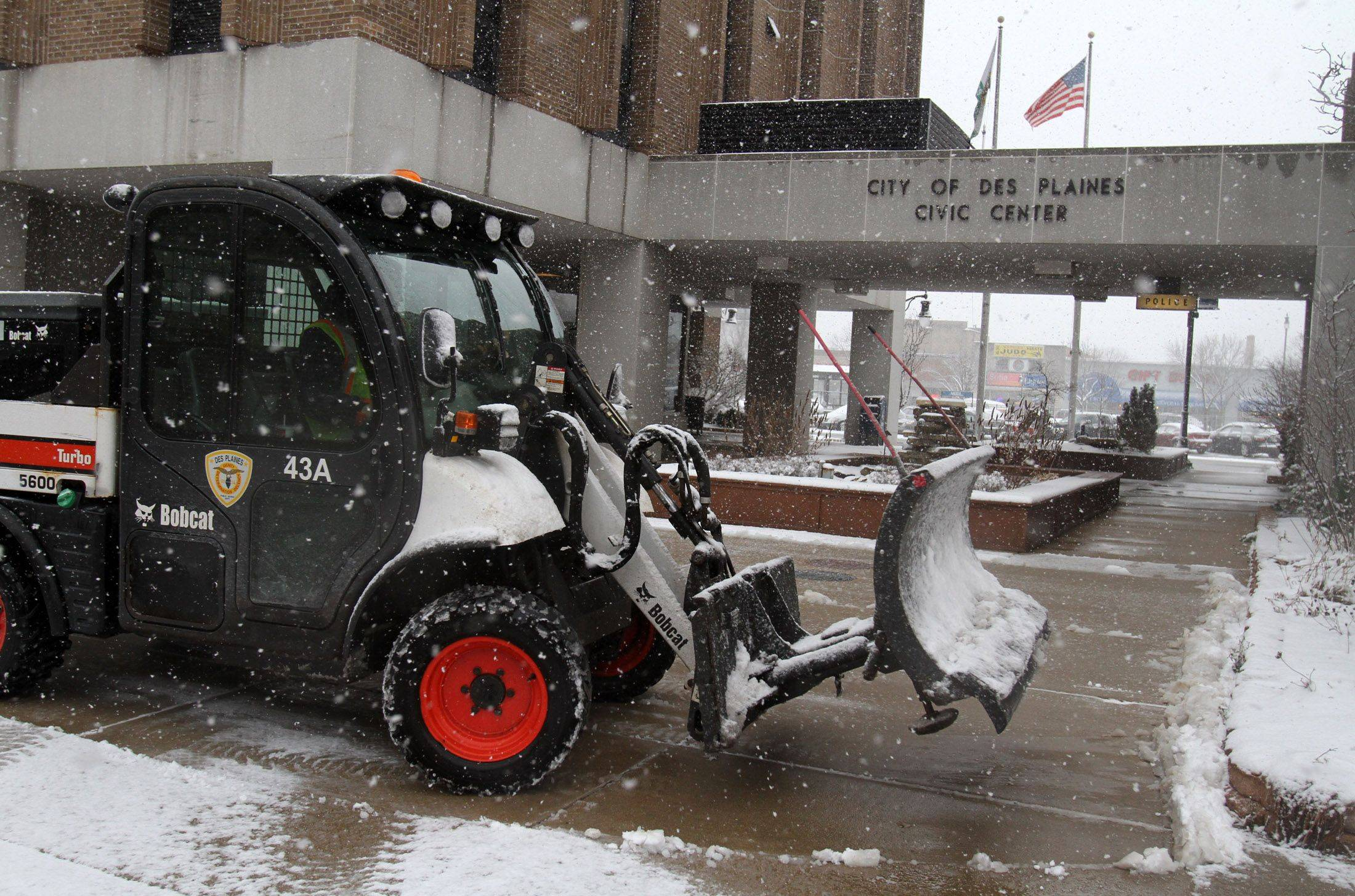 Barry Horner with Des Plaines Public Works and Engineering Department plows the sidewalk near City of Des Plaines Civic Center.